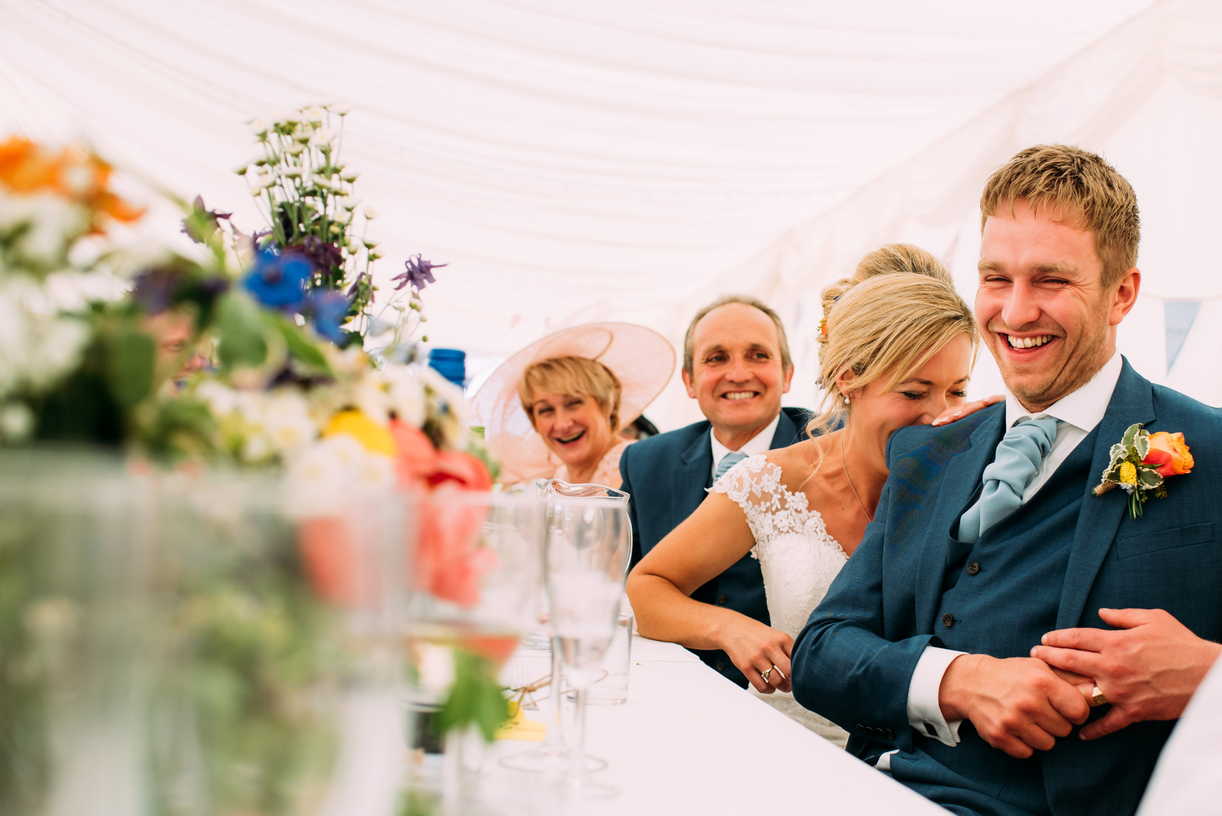 the bride laughs on the grooms shoulder during the speeches
