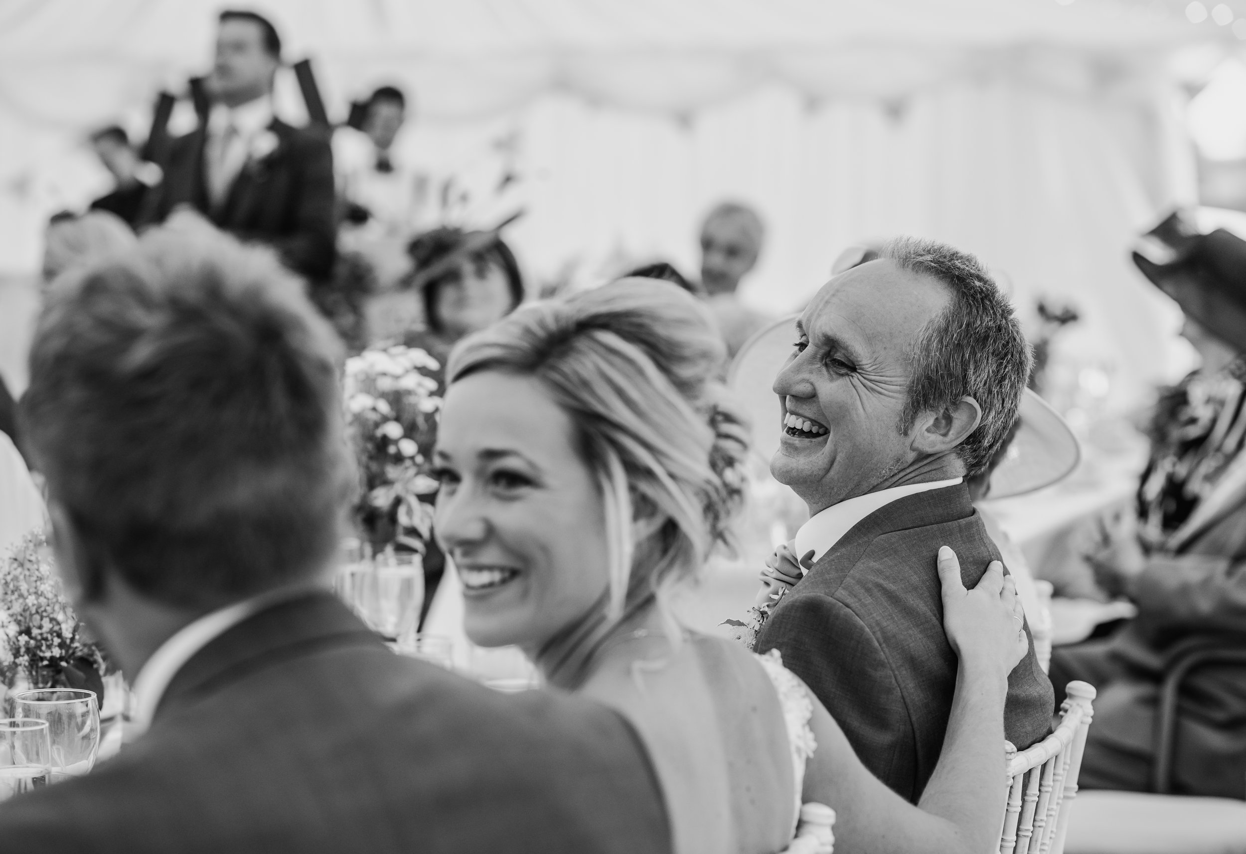bw photo. Brides hand on her fathers back as he laughs