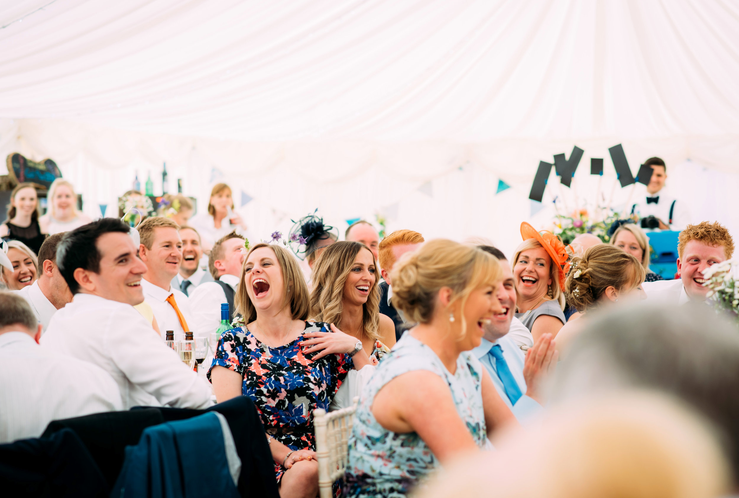 guests laughing during the best man speech