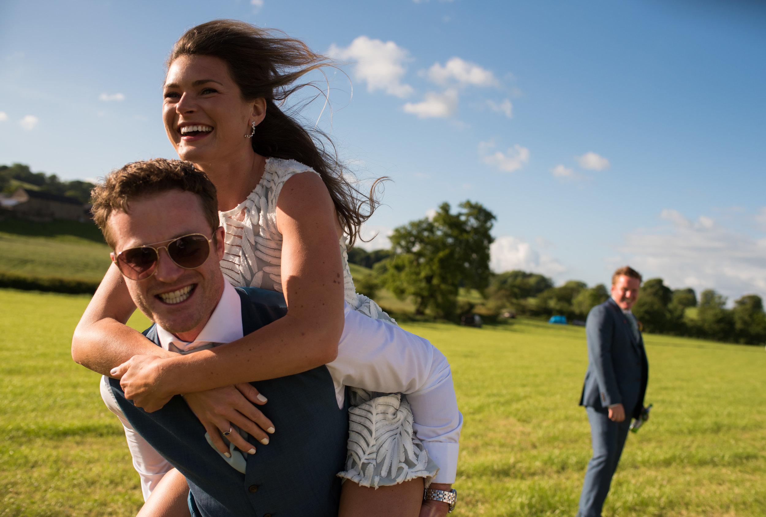 a 'piggybacking' couple run past the camera