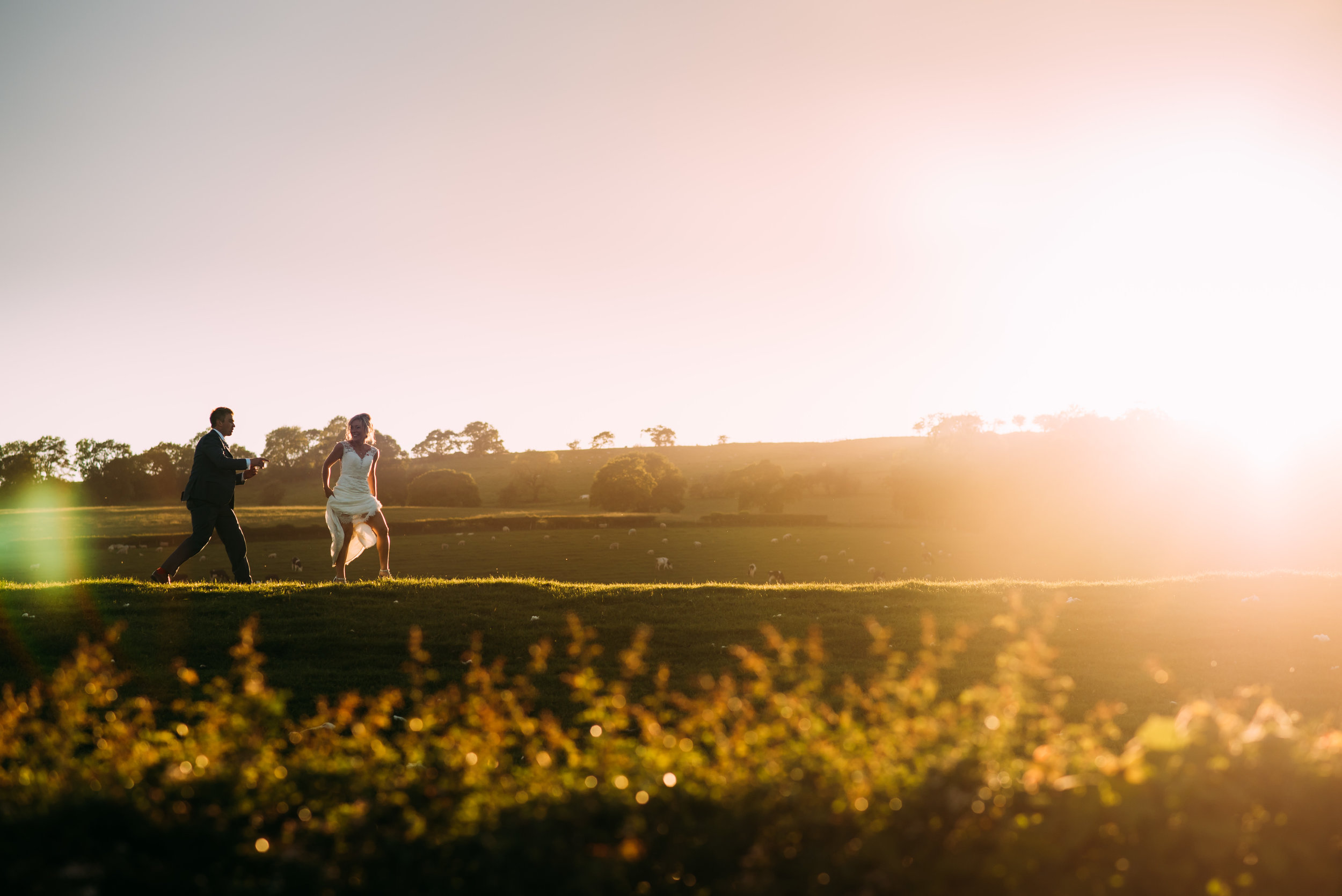 sunset photo of the bride and groom running up a hill in the distance