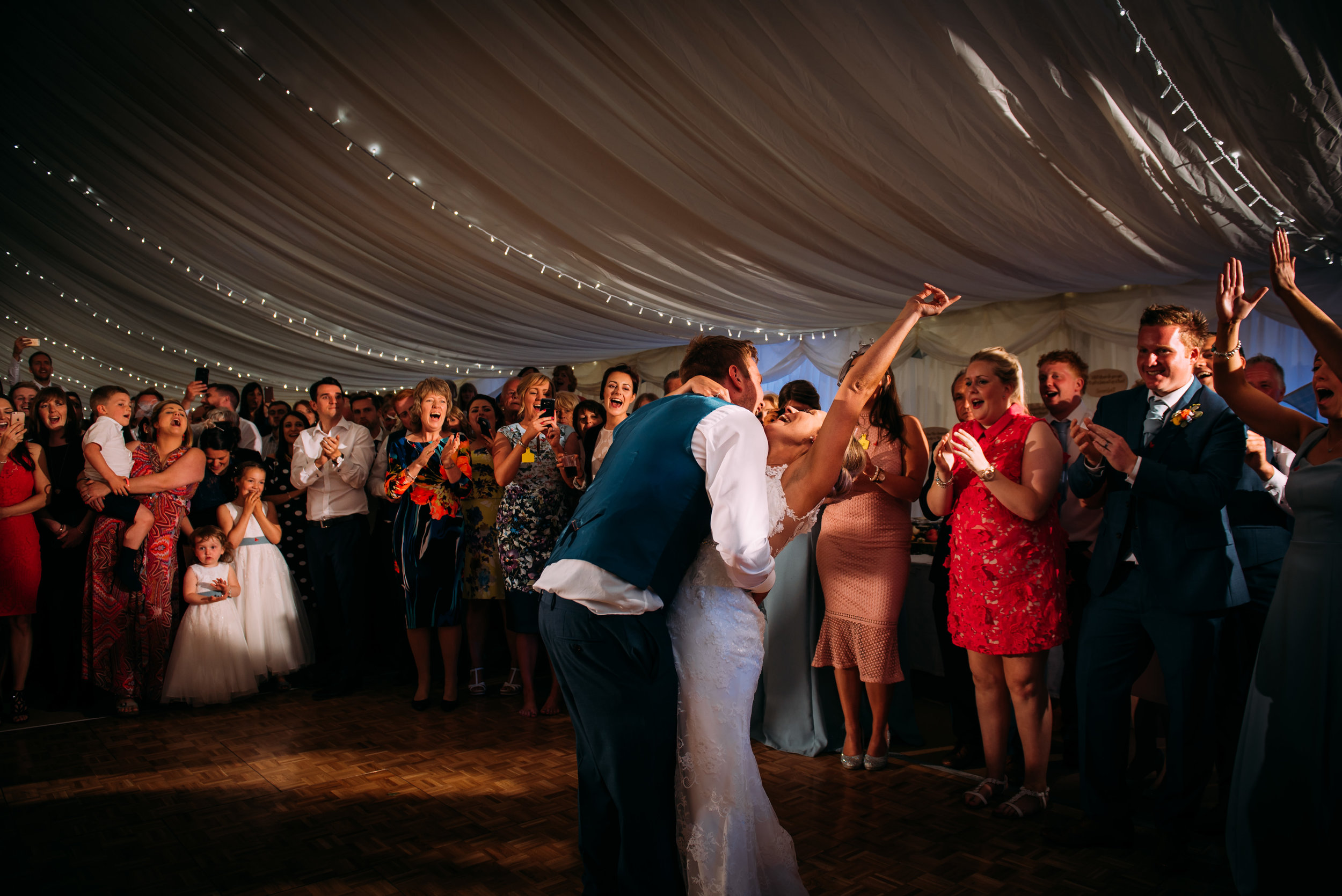 the groom tips his bride during the first dance. The guest in the background cheer