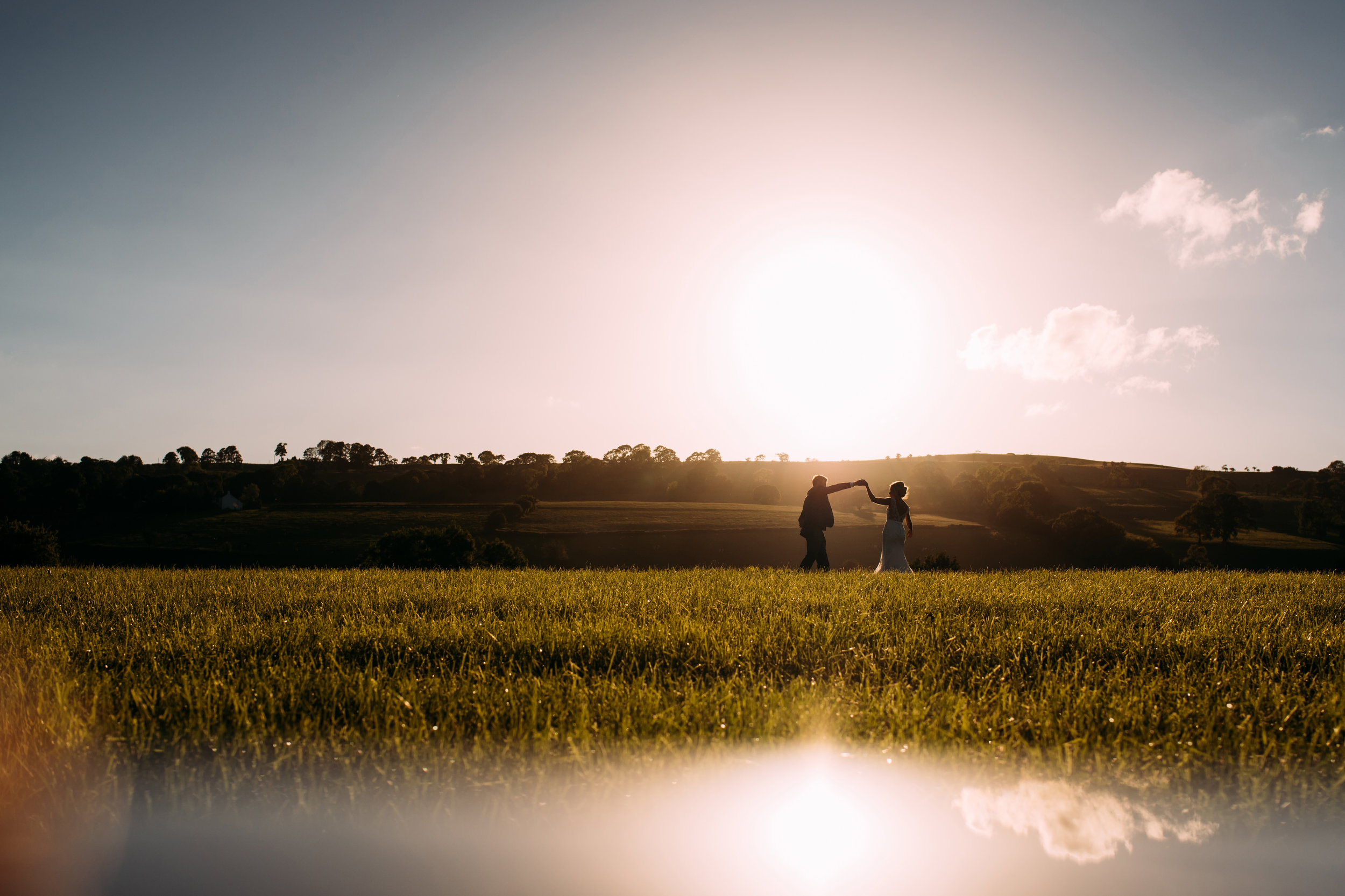 couple practise their first dance in the field at sunset