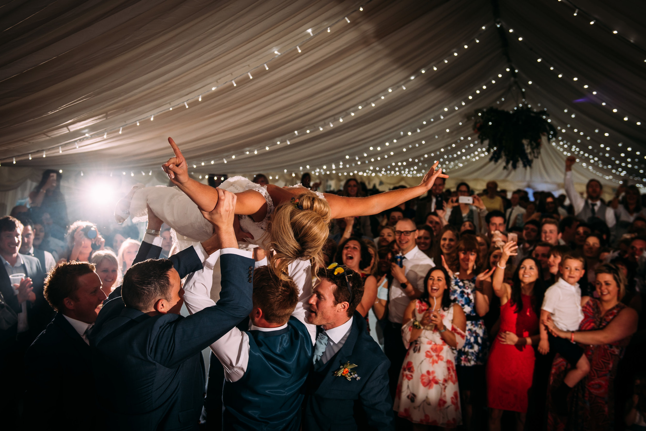 all the guest cheering at the bride being lifted