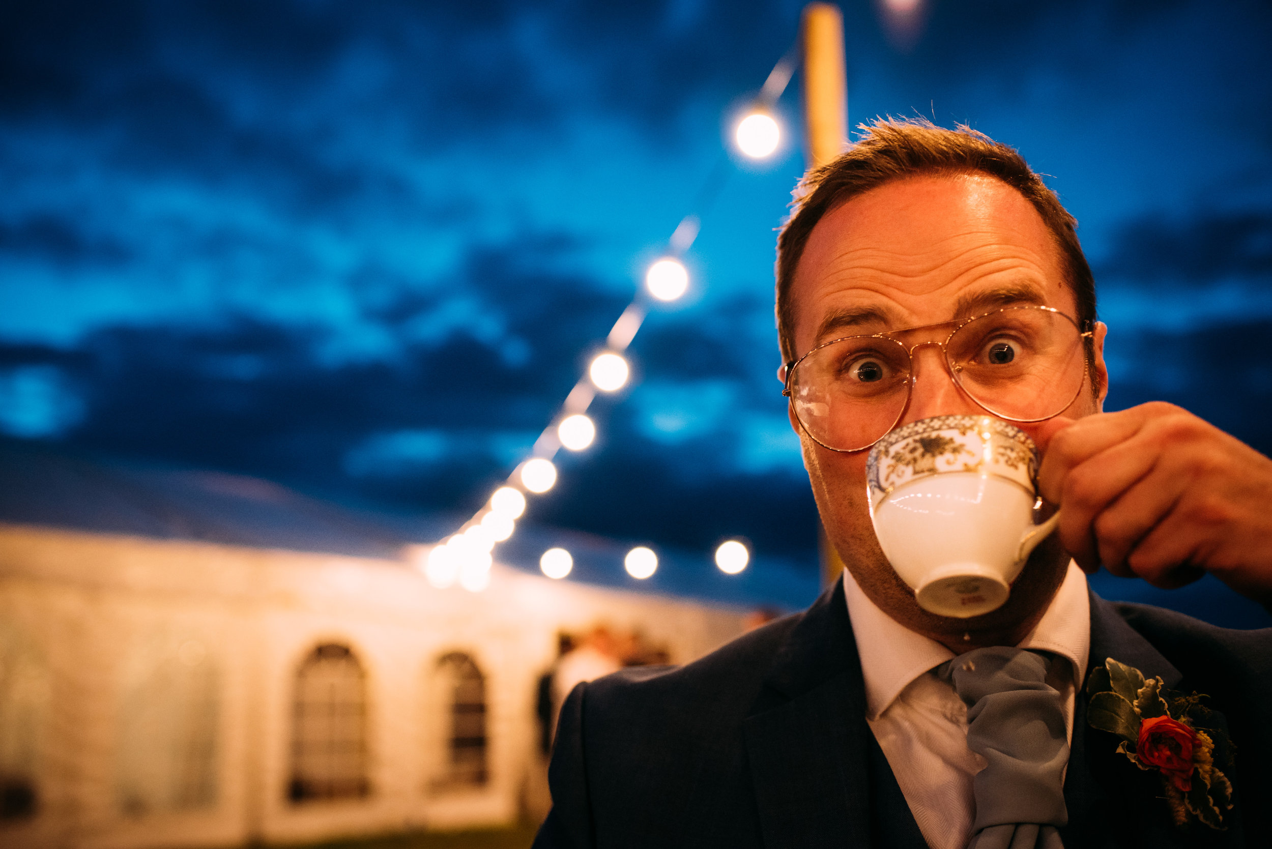 close up of a drunk guest drinking tea out of 'fine china'