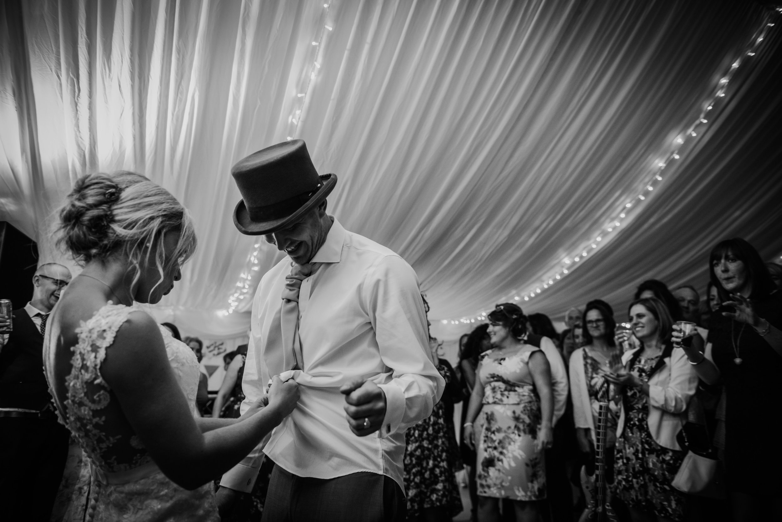bw photo of the bride unbuttoning the grooms shirt