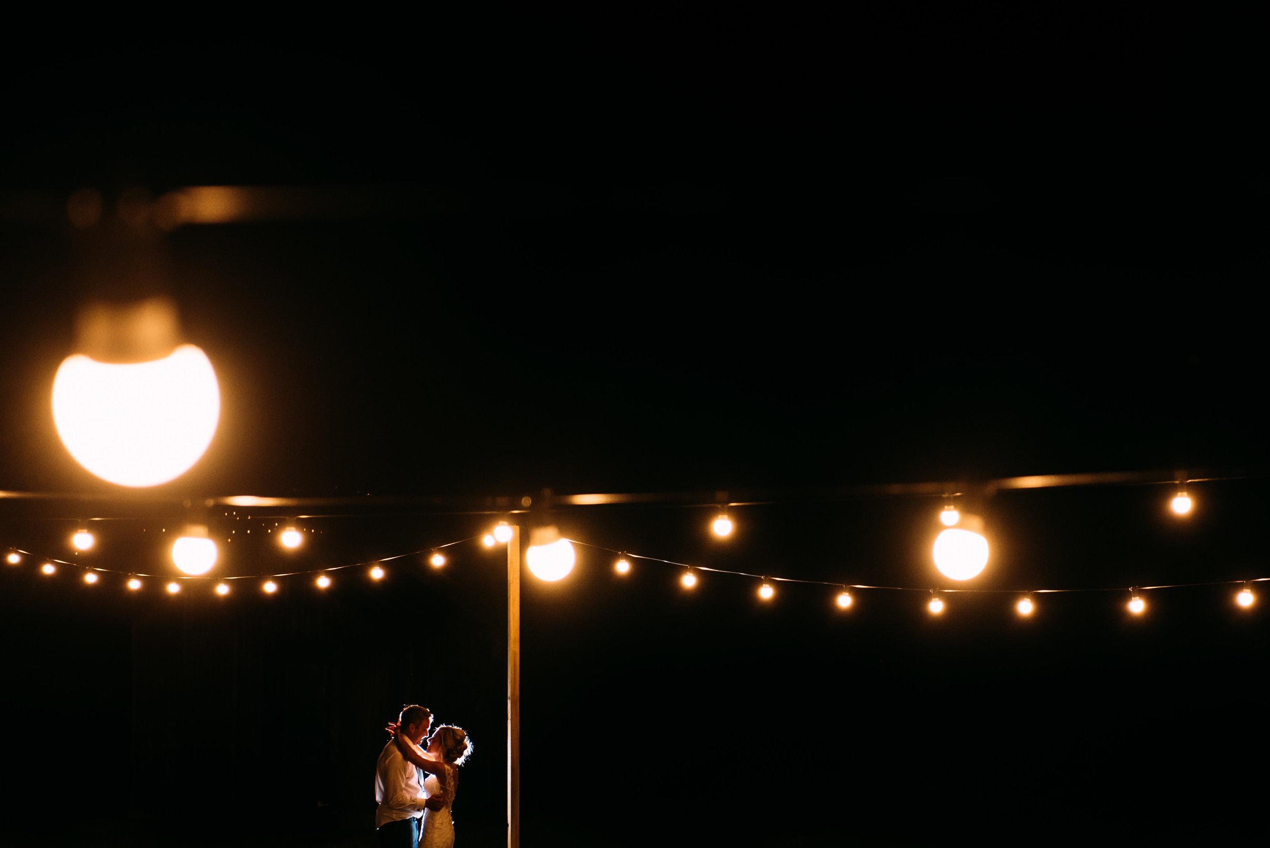 bride and groom dance under festoon lights