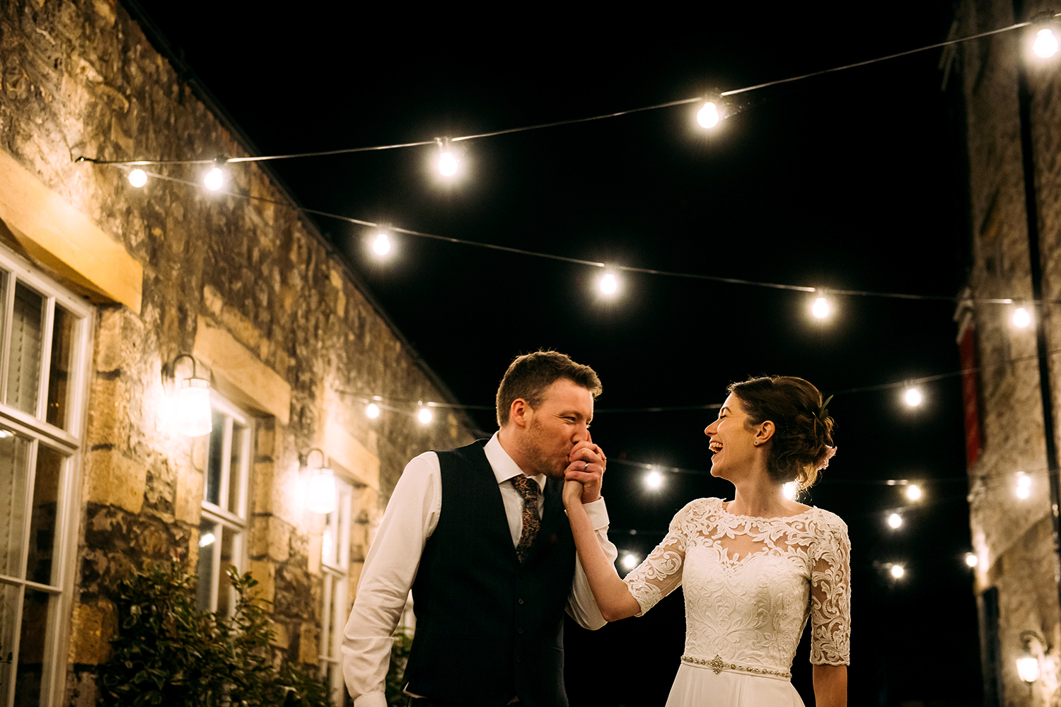 Couple at Holmes mill with the groom kissing the brides hand under the festoon lights
