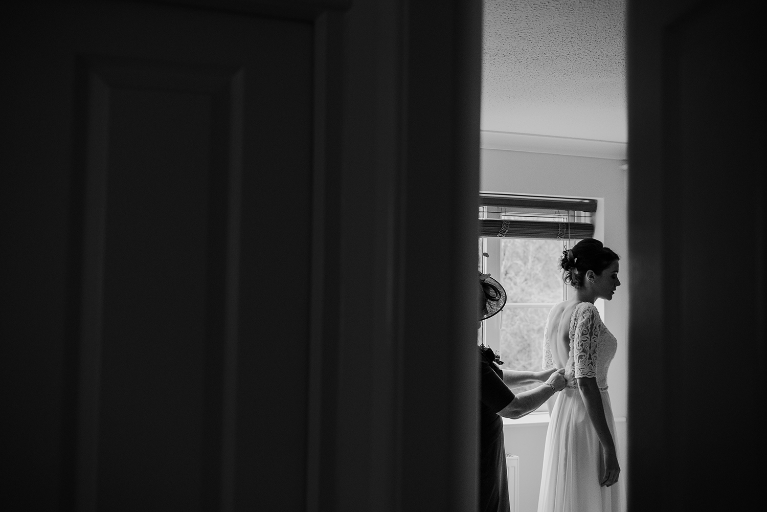 BW photo taken through a gap in the door of the brides mum doing up her dress