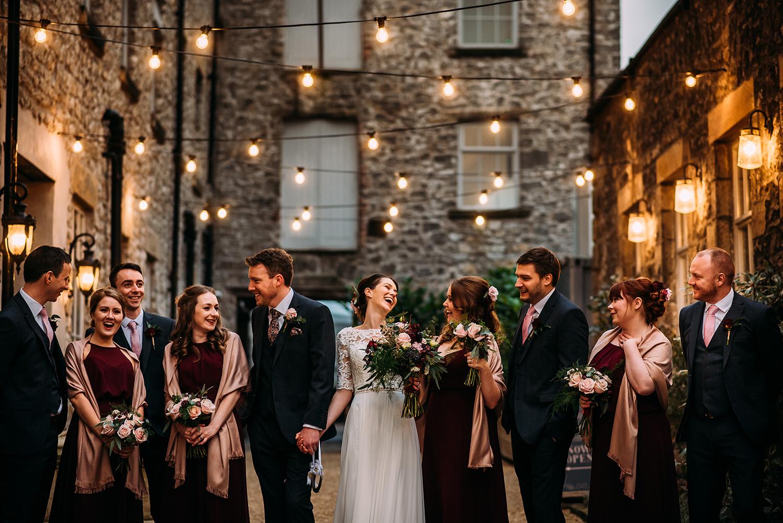 bridal party group shot under festoon lights