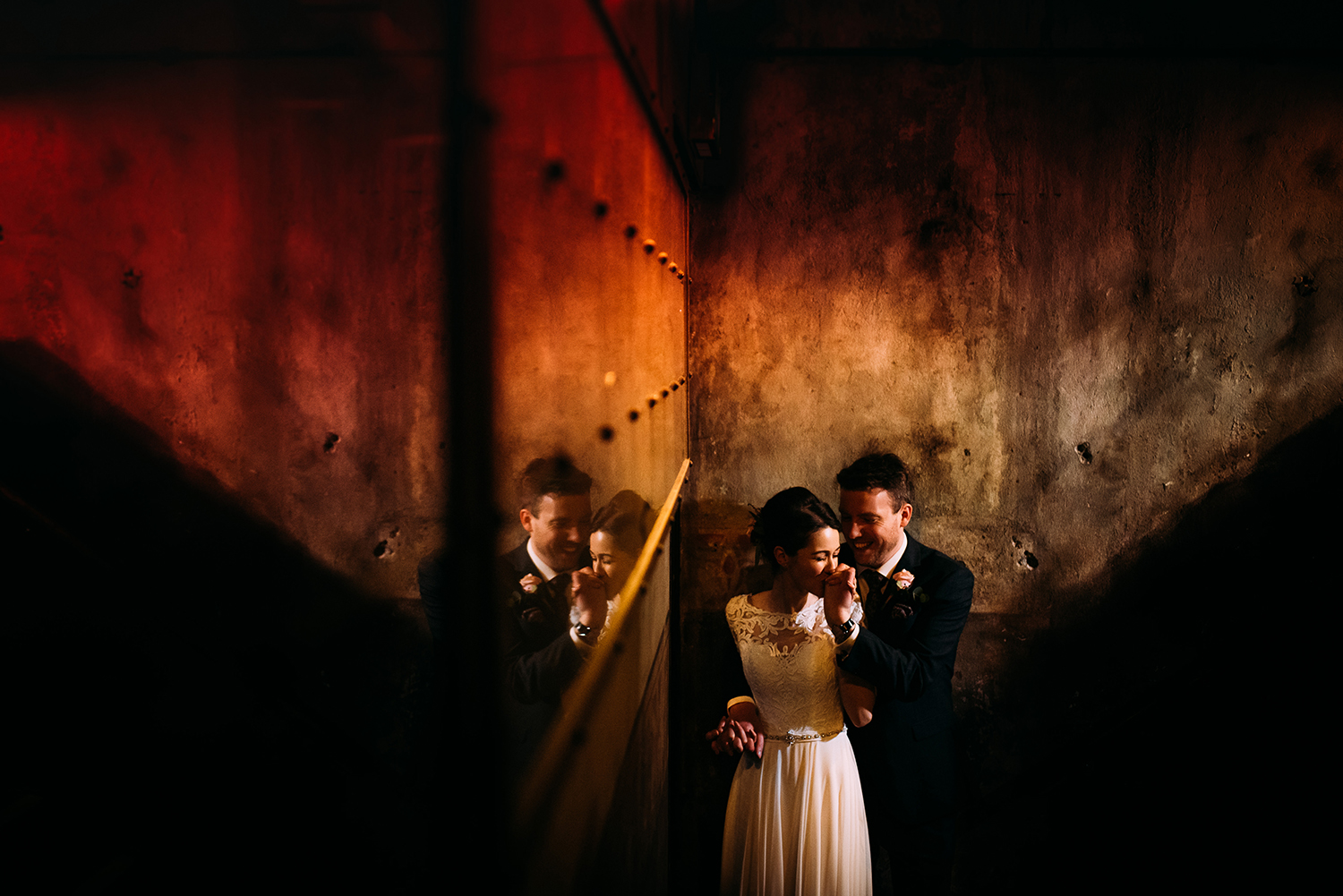 couple photo in a corner of the industrial room. Bride kissing grooms hand