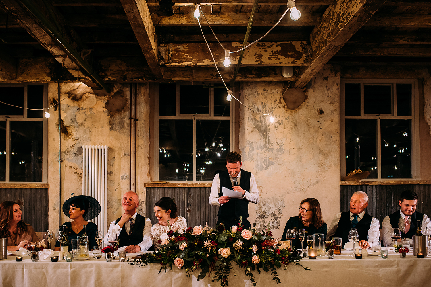 wide shot of groom speech with the top table laughing