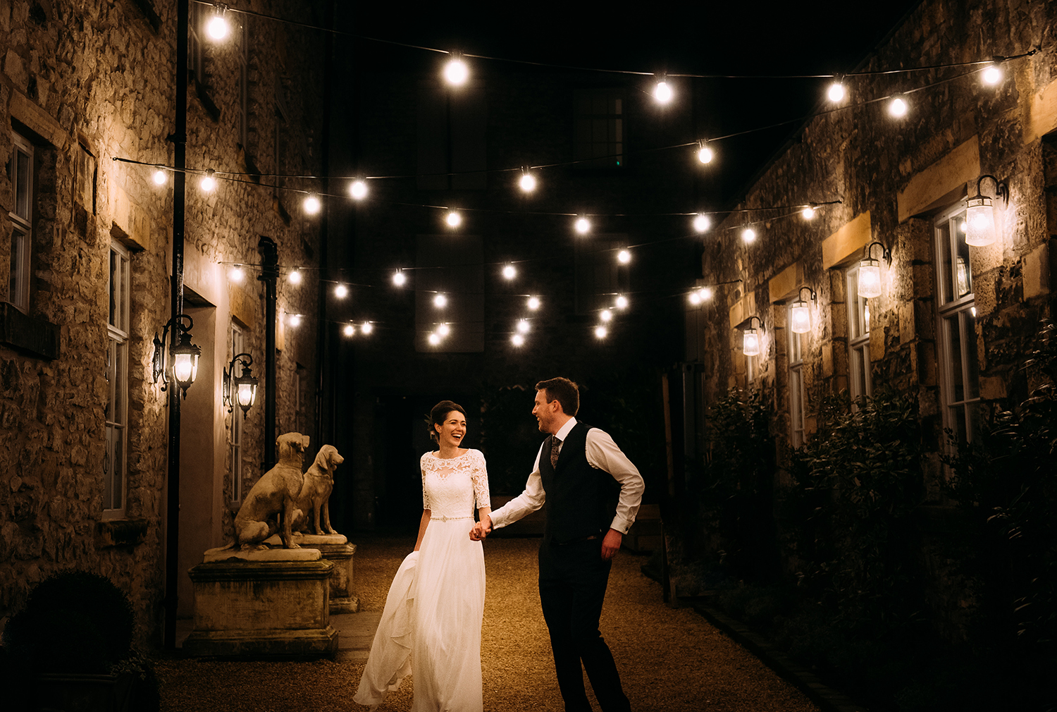relaxed photo of the bride and groom having a stroll at night under the festoon lights