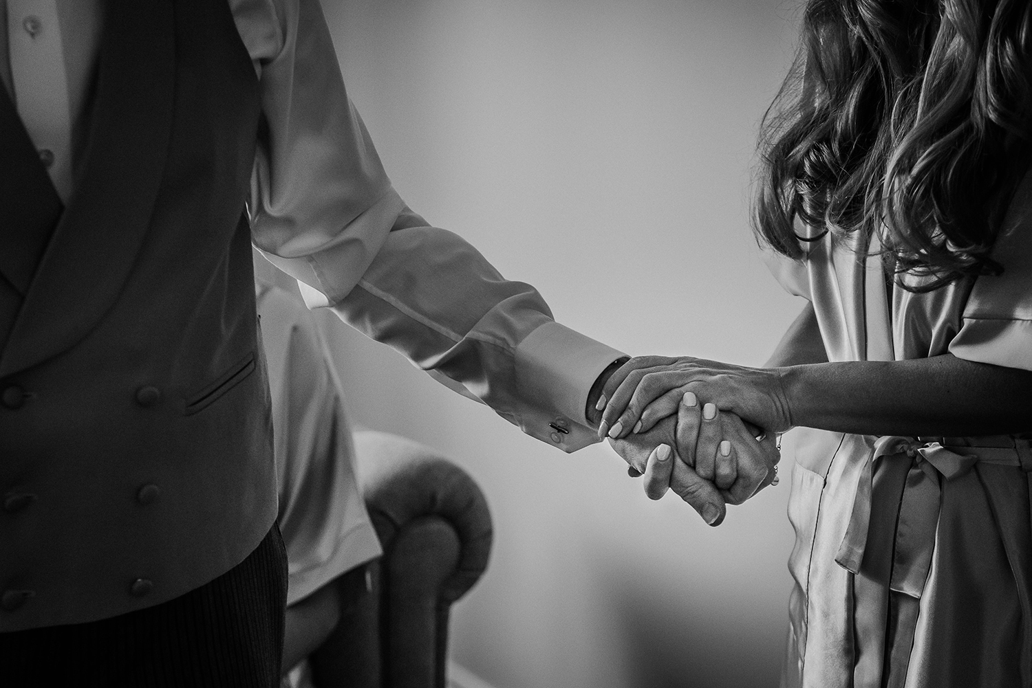 BW photo of bride and her dad holding hands
