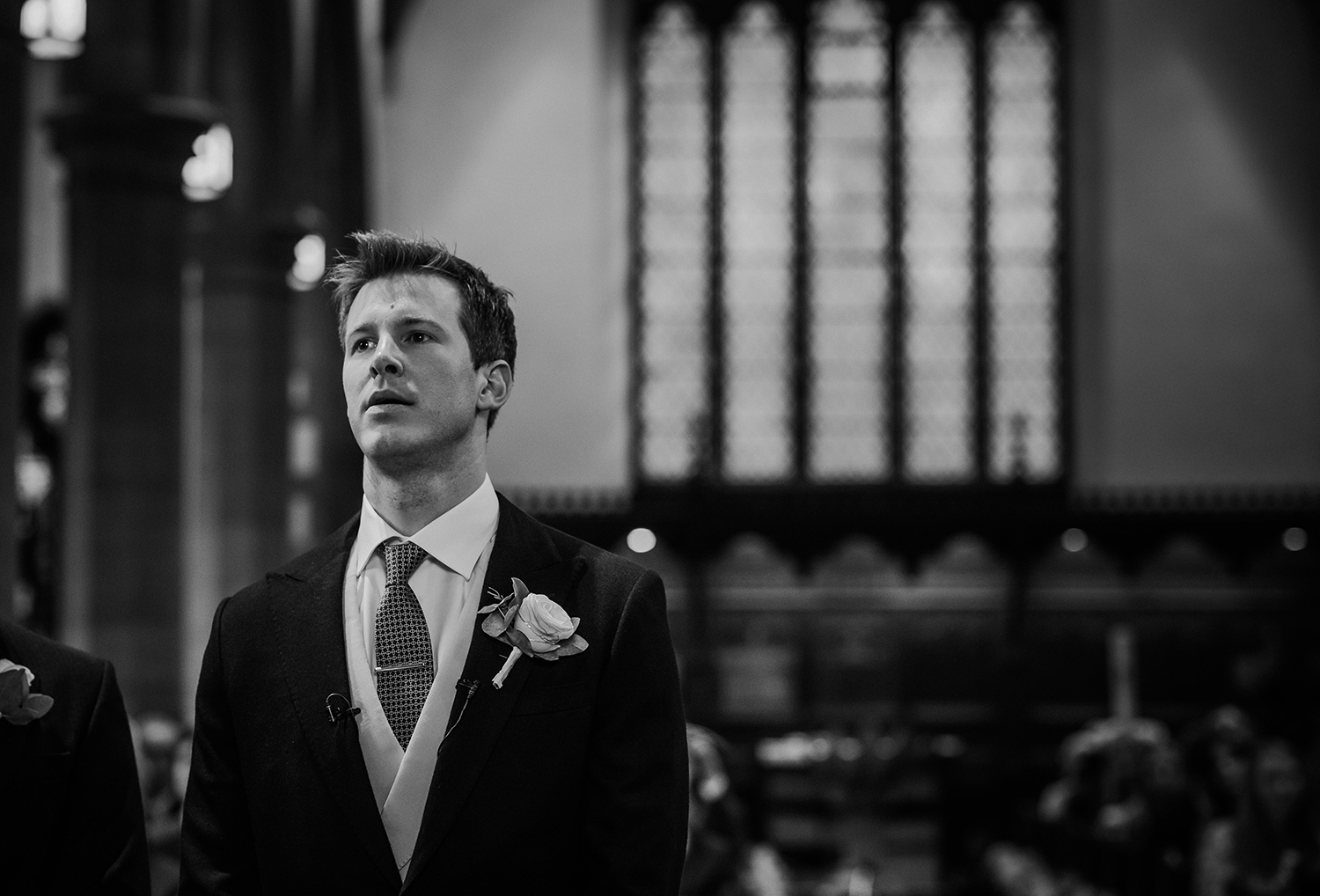 BW photo of nervous groom in church
