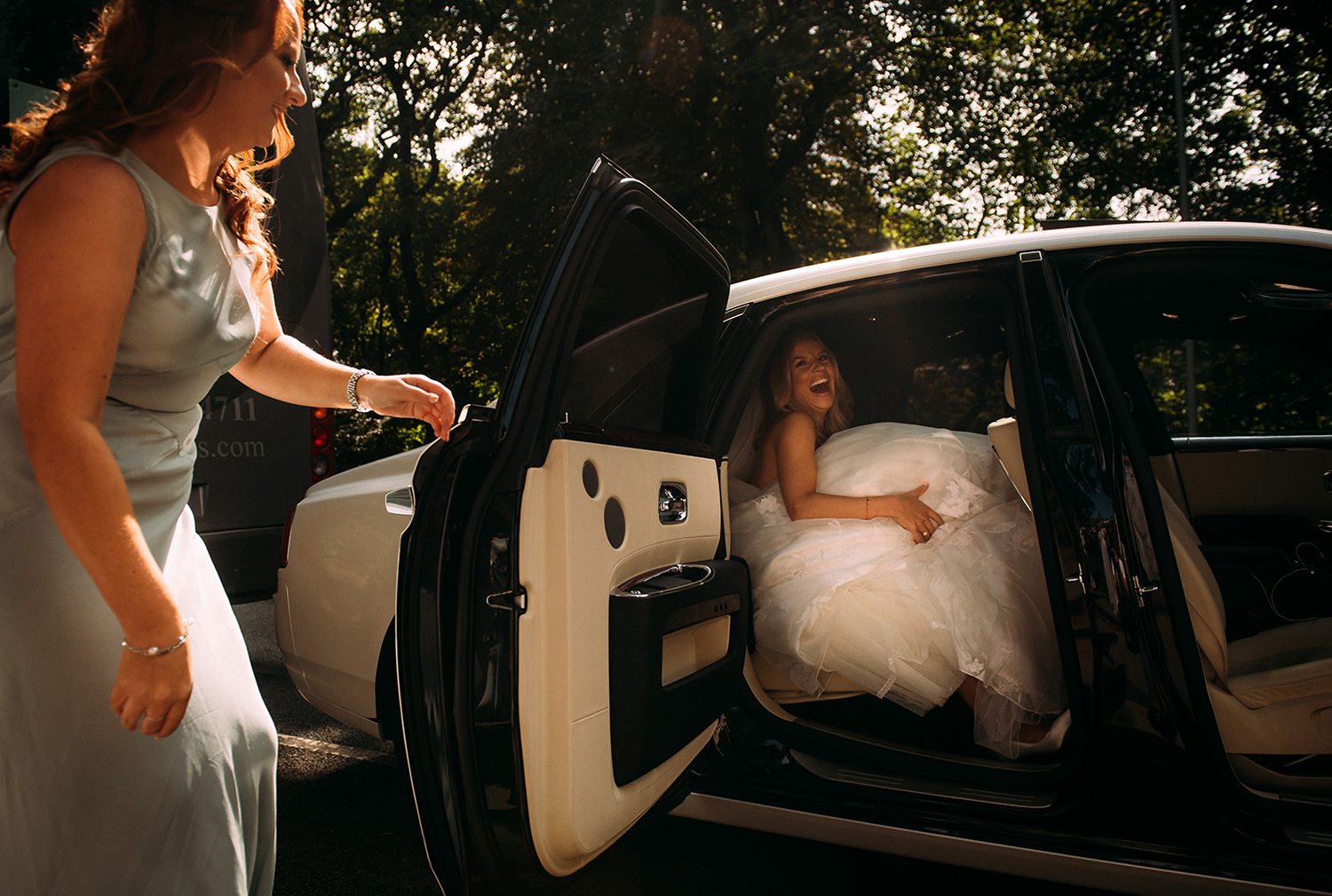 brides sister helping her out of the wedding car