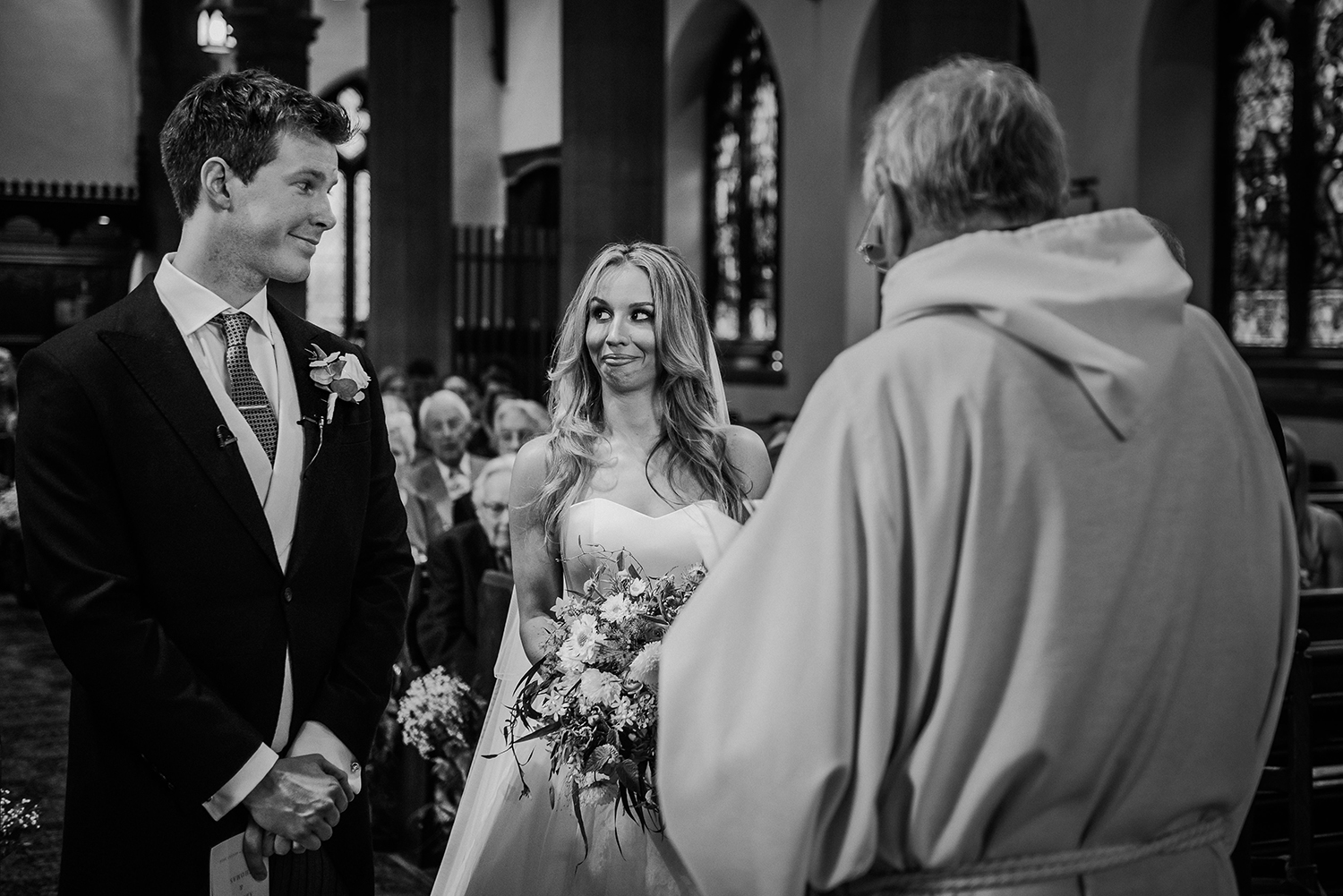 BW photo of bride and groom pulling funny faces at each other