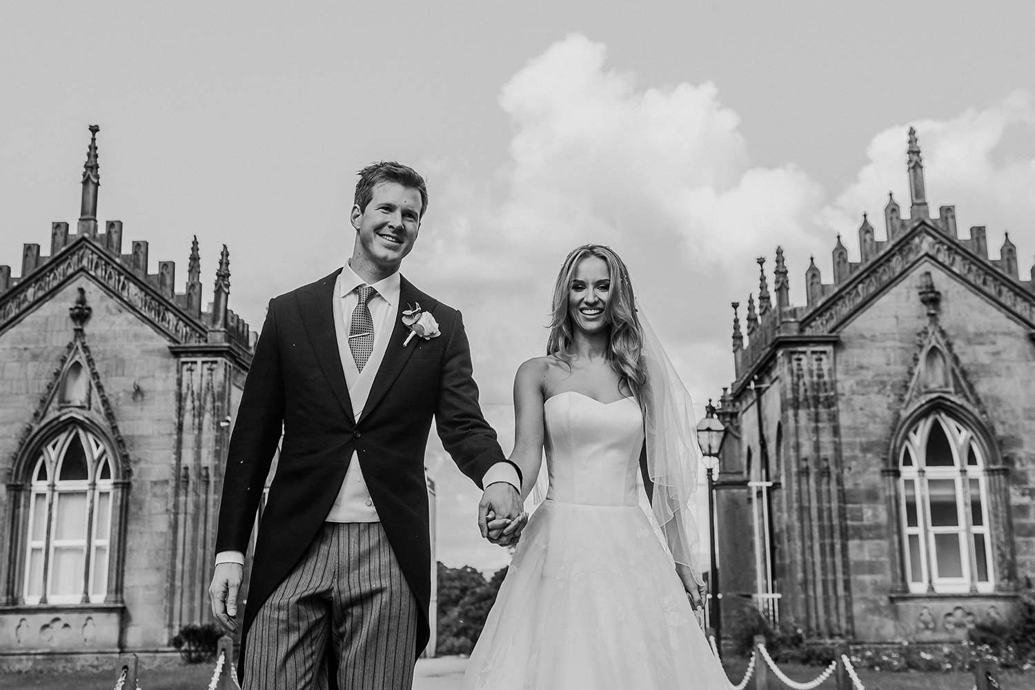 BW photo of bride and groom at the venue gates