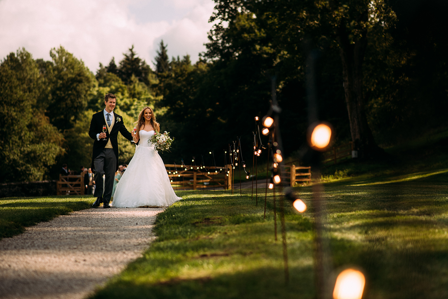 bride and groom walking along a fairy lit path to the marquee