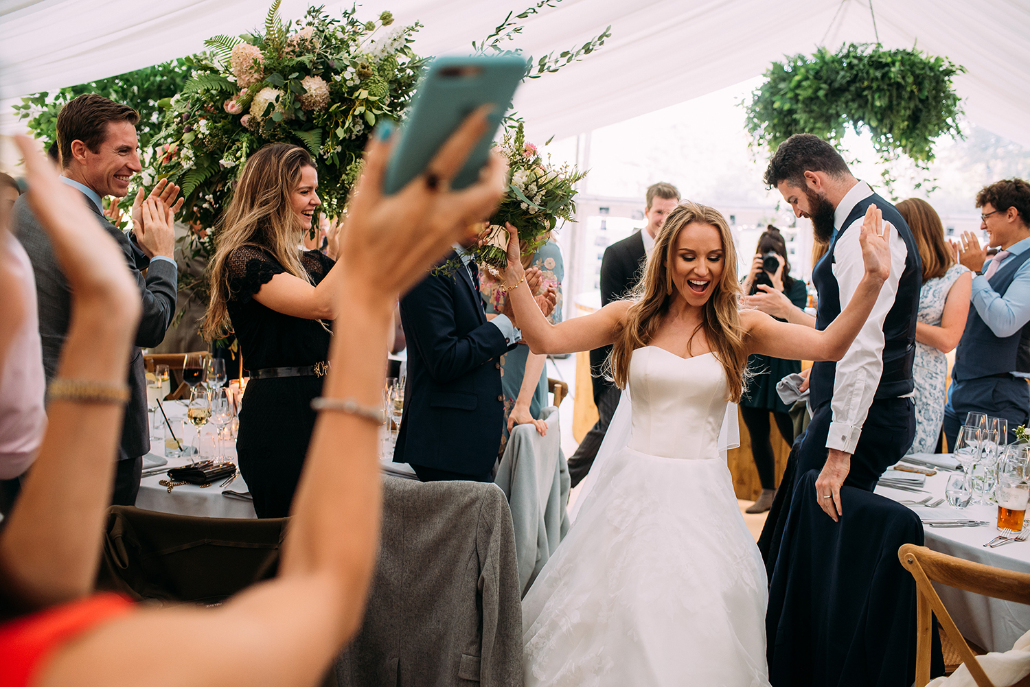 bride enters the reception with her hands in the air