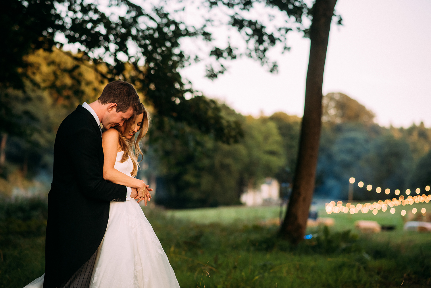 bride and groom cuddle with the venue in the background