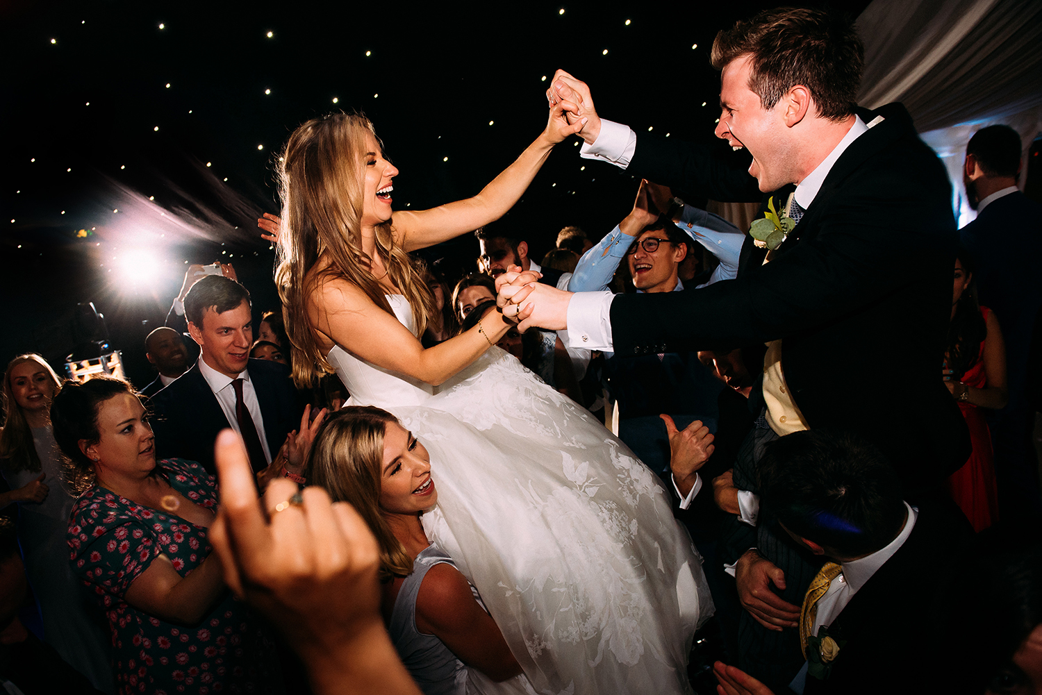 bride and groom holding hands whilst on guests shoulders