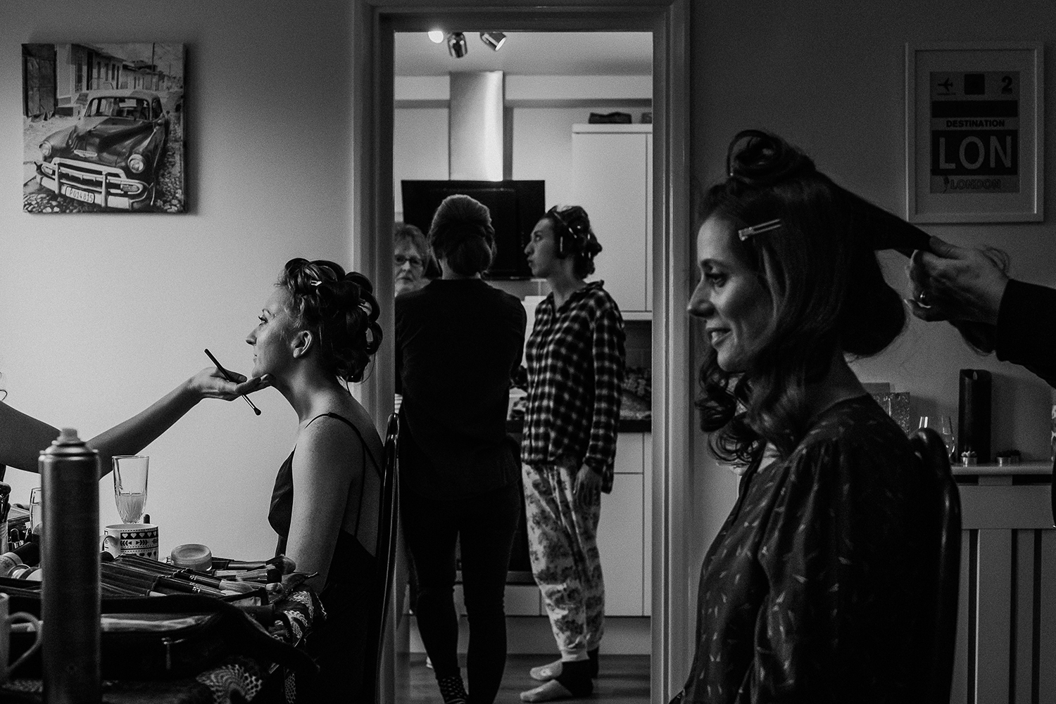 BW photo of bridal prep. Bride and bridesmaids on either side of the frame with friends in the centre framed by the kitchen door