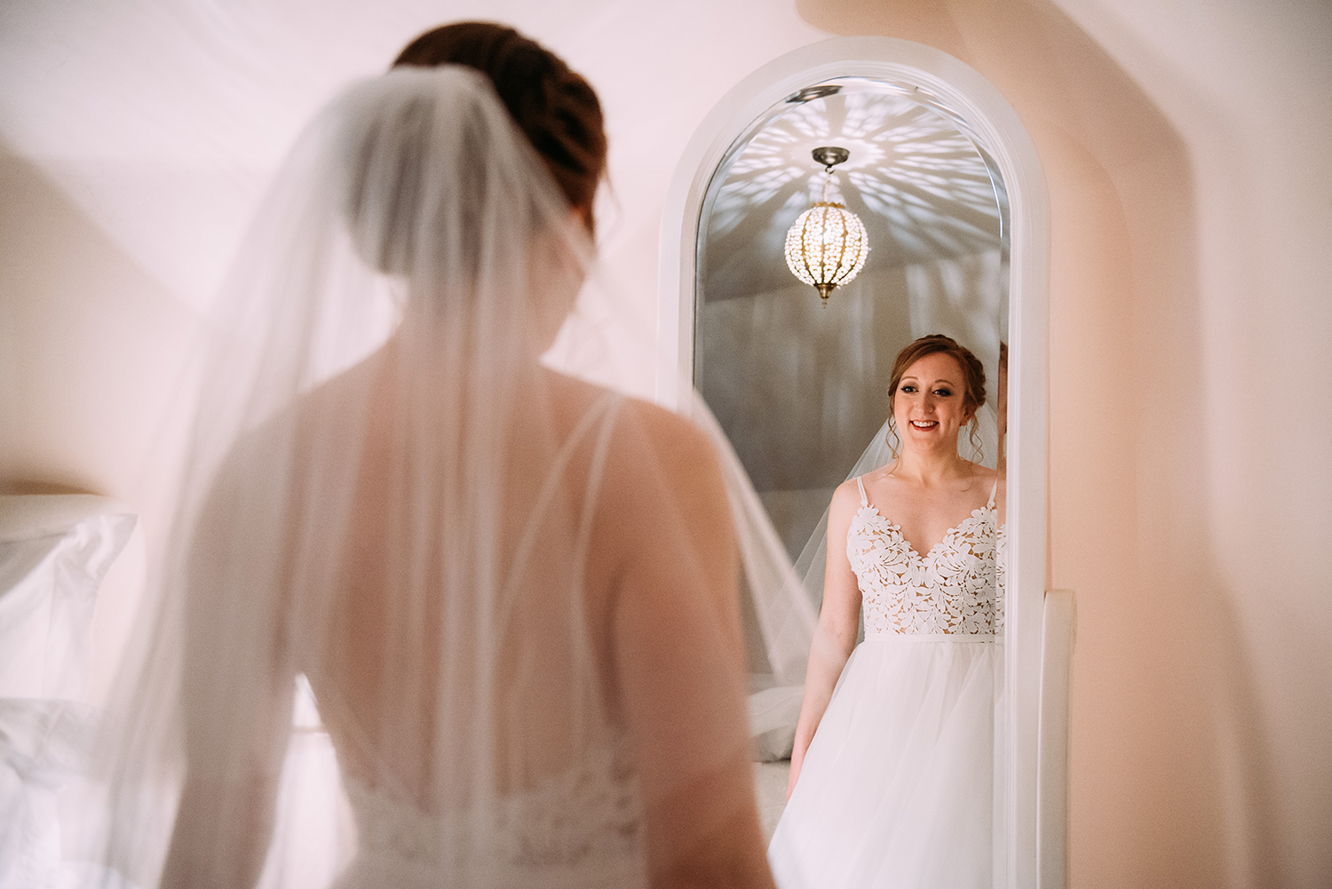 bride in dress looking in the mirror