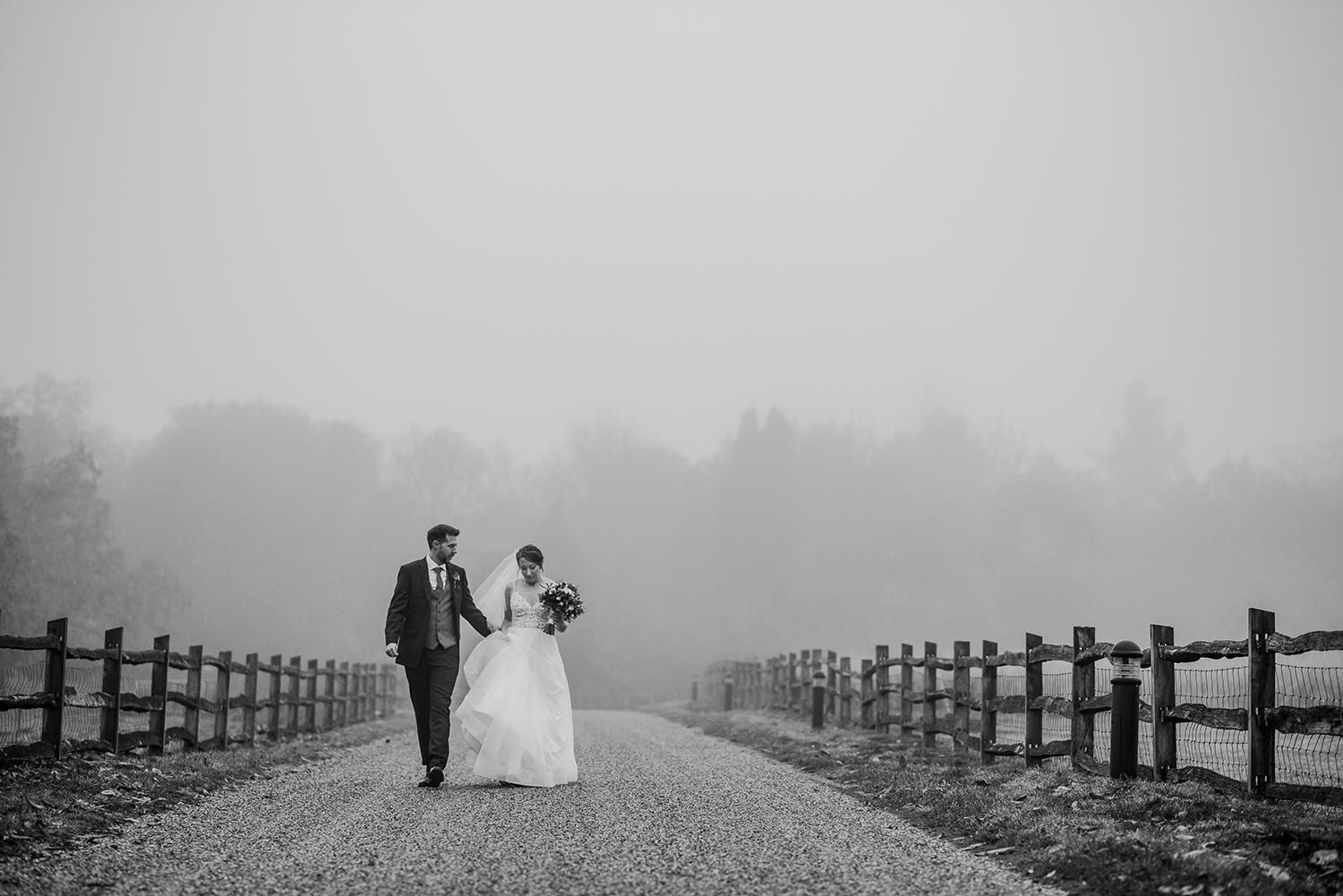 BW photo of couple walking down the driveway in the mist