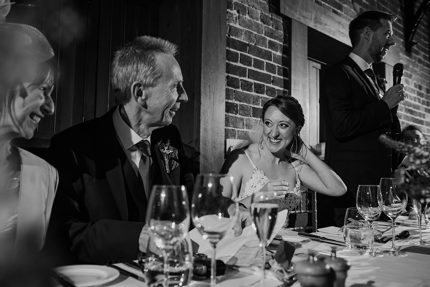 BW photo, bride smiling at her dad after his speech