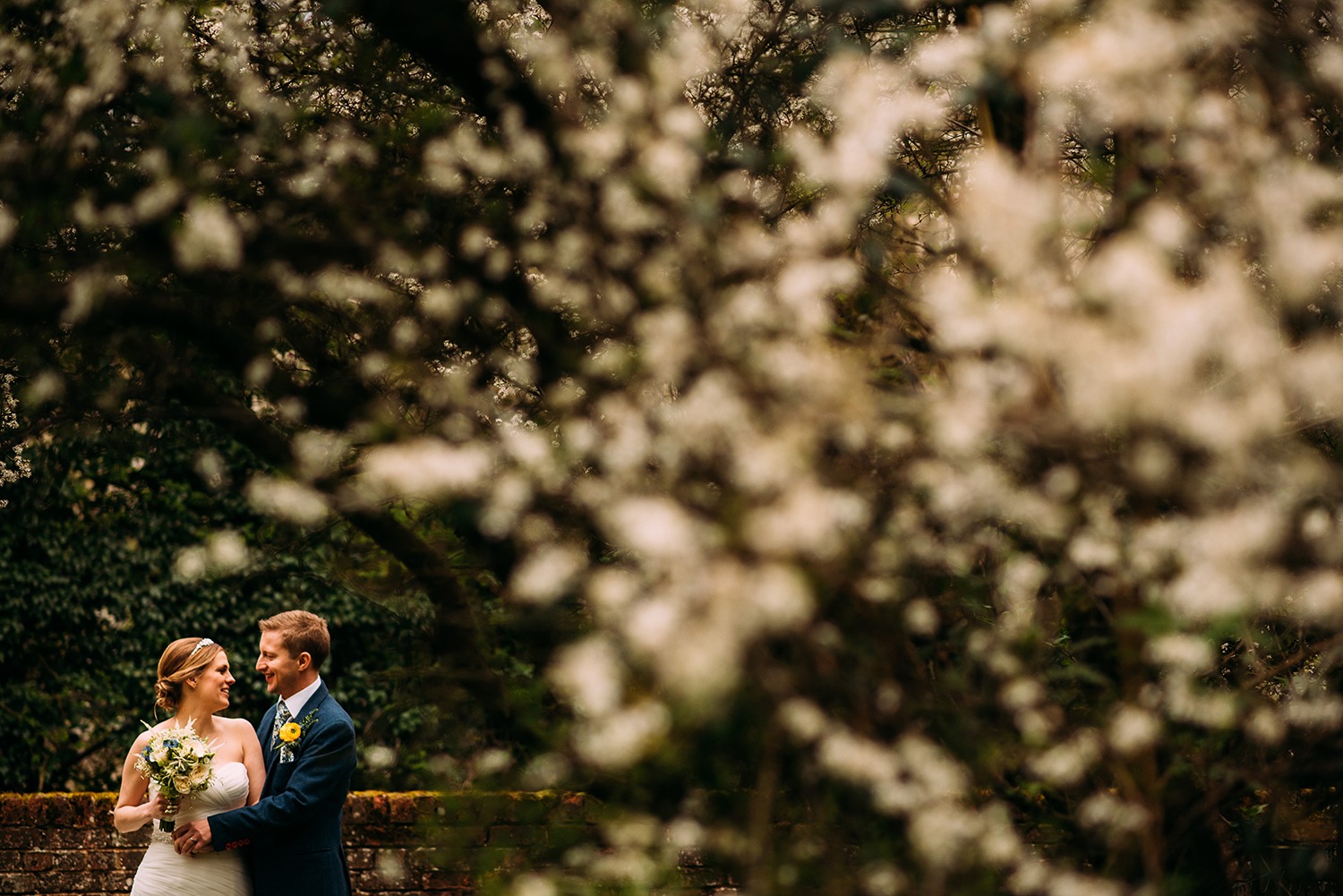 couple photo in the bottom left corner surrounded by white flowers from the tree