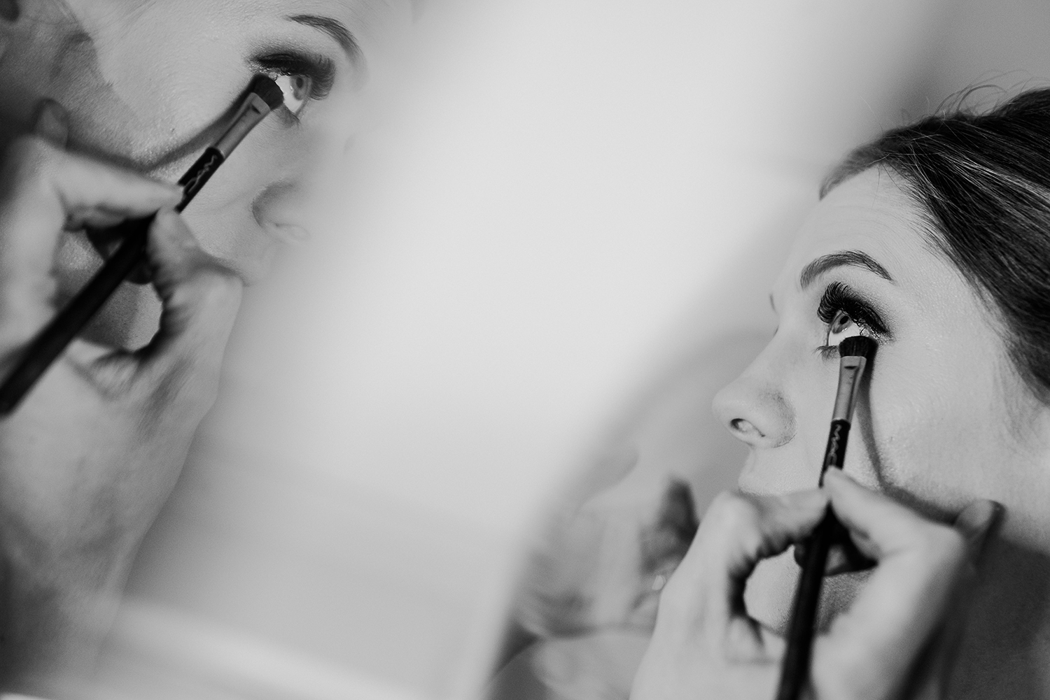 bw photo of bride having eye liner put on with a reflection