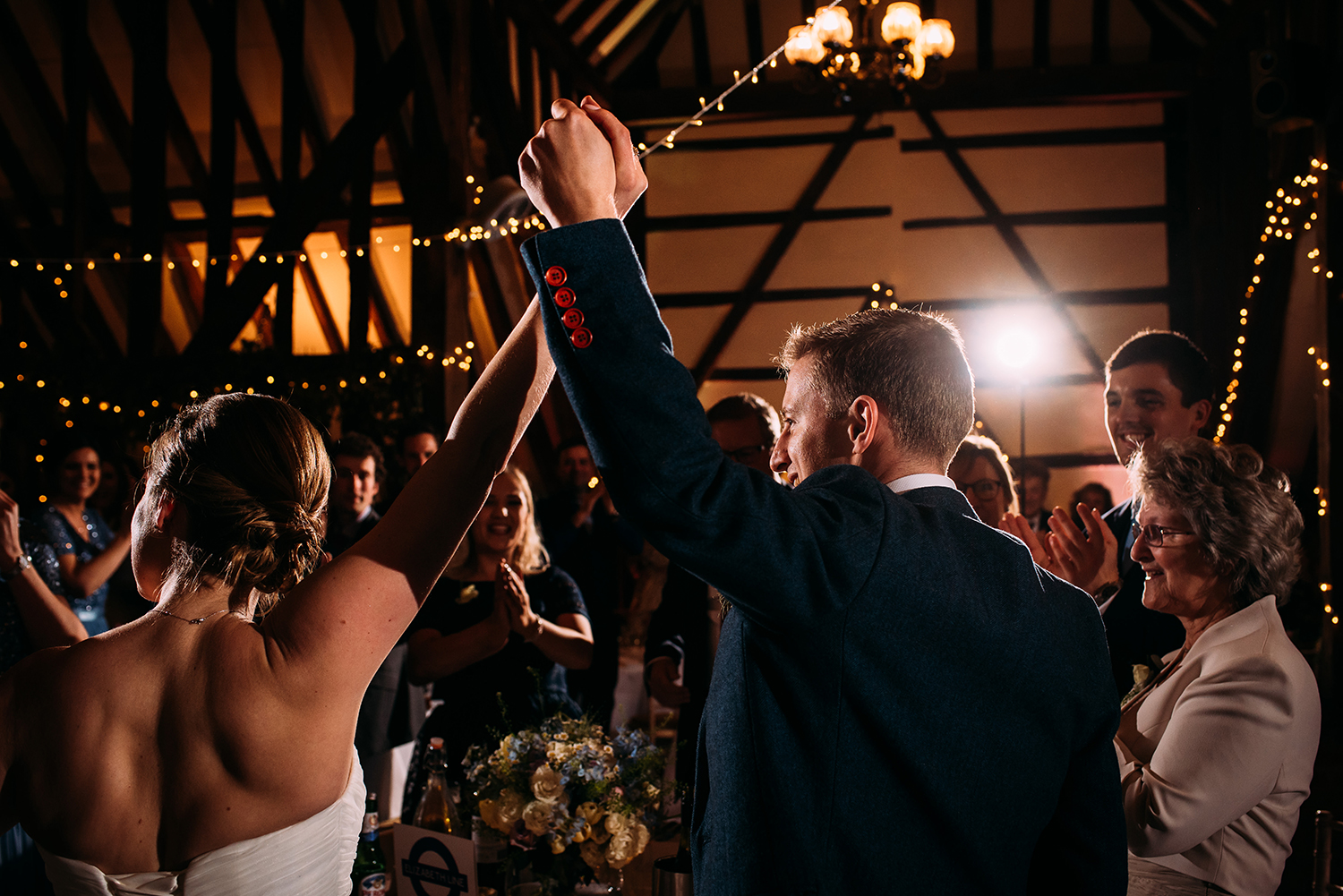 bride and groom lift their holding hands in the air as they arrive in the room for their reception