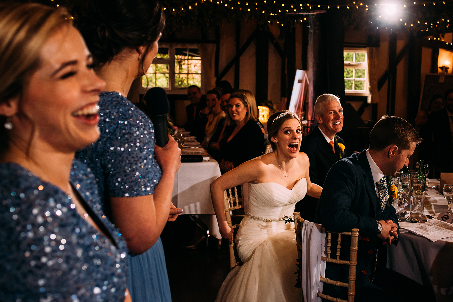focus on brides shocked face during the bridesmaids speech with the bridesmaids laughing in the foreground