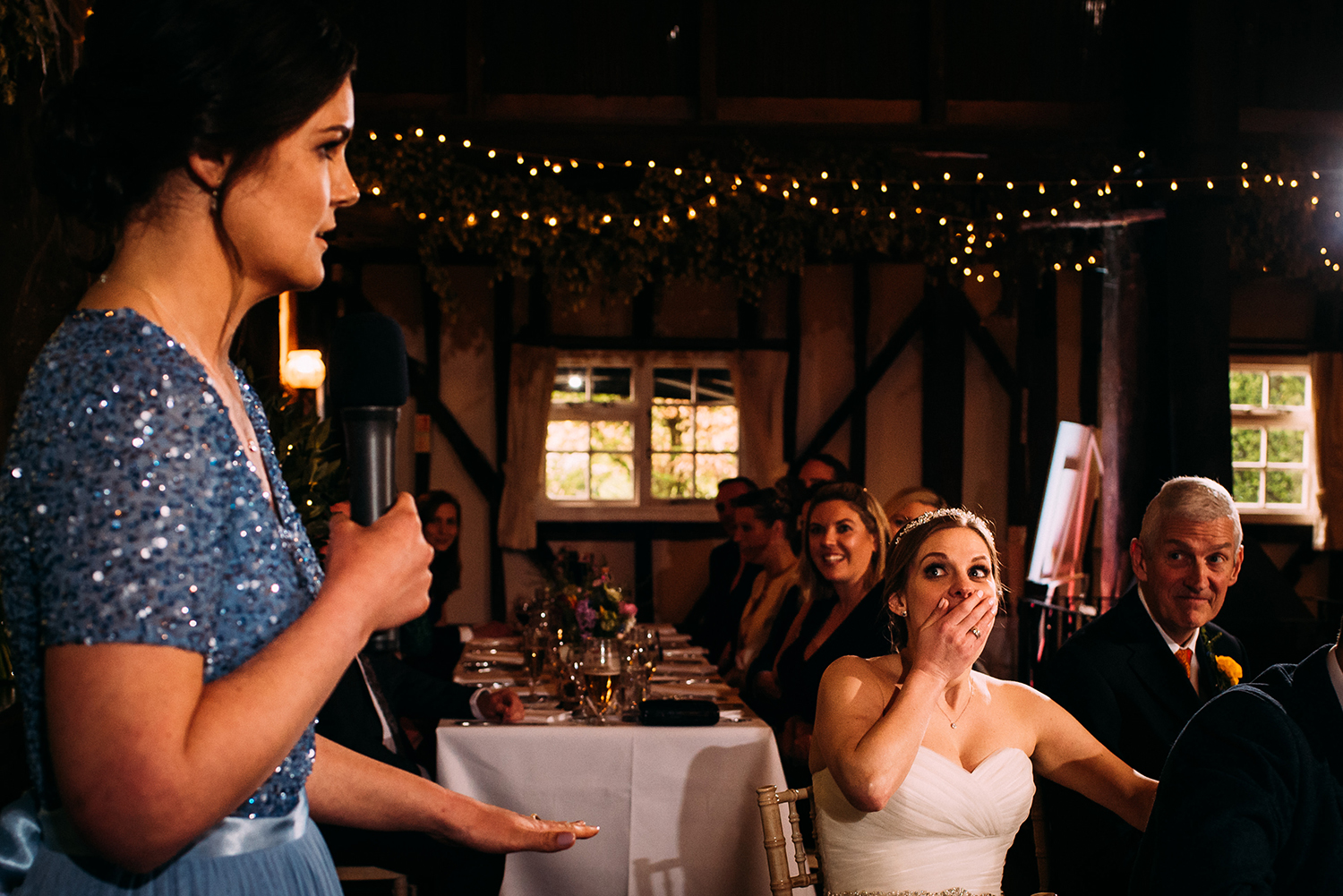 bride covers her mouth with her hand during the speeches