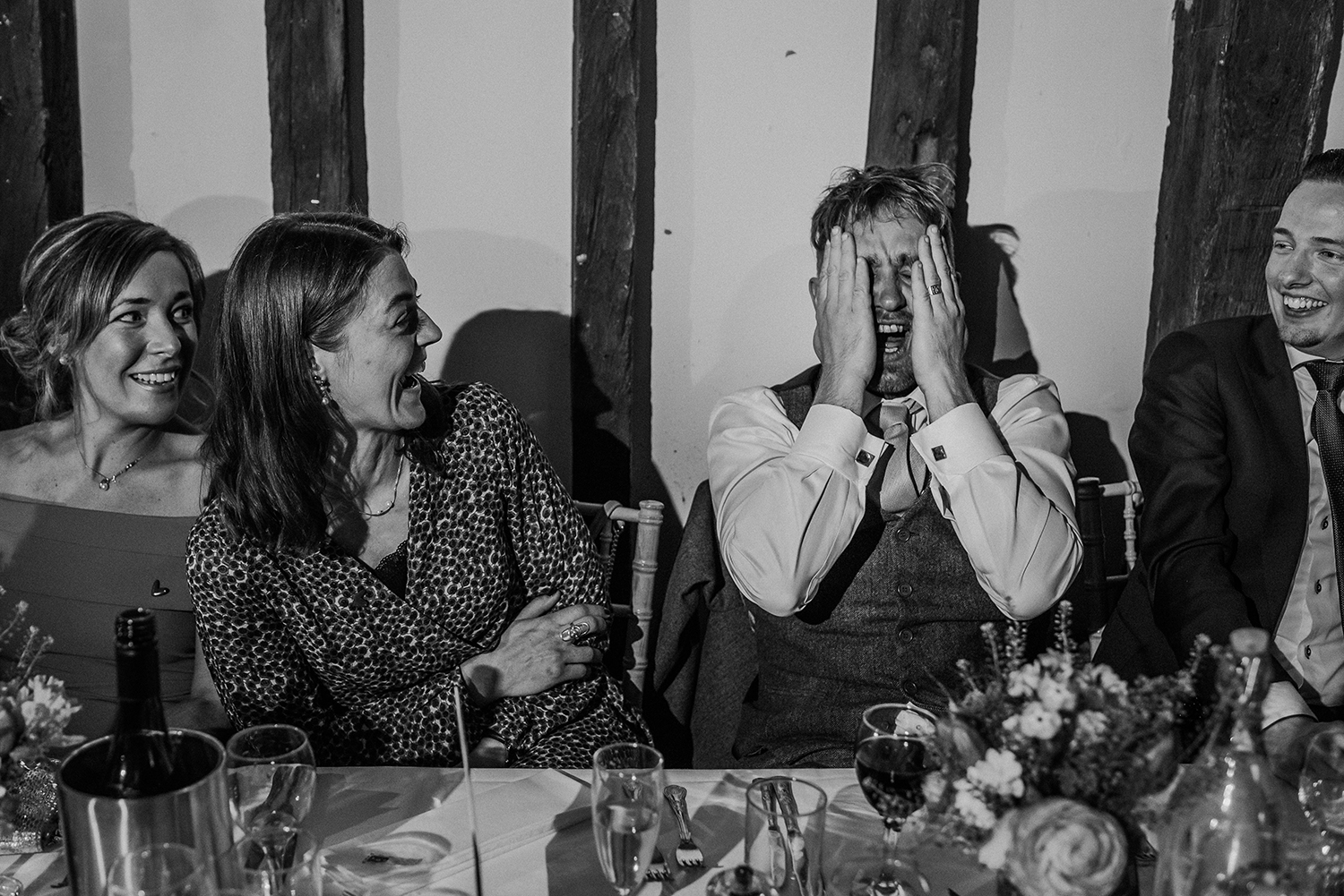 bw photo of an embarrassed guest with two ladies sat next to him laughing