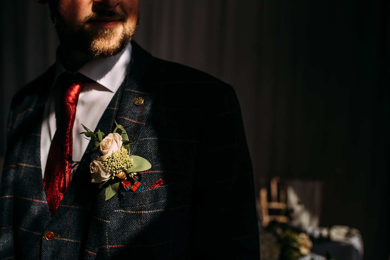 groom stood in nice light showing his wedding flower