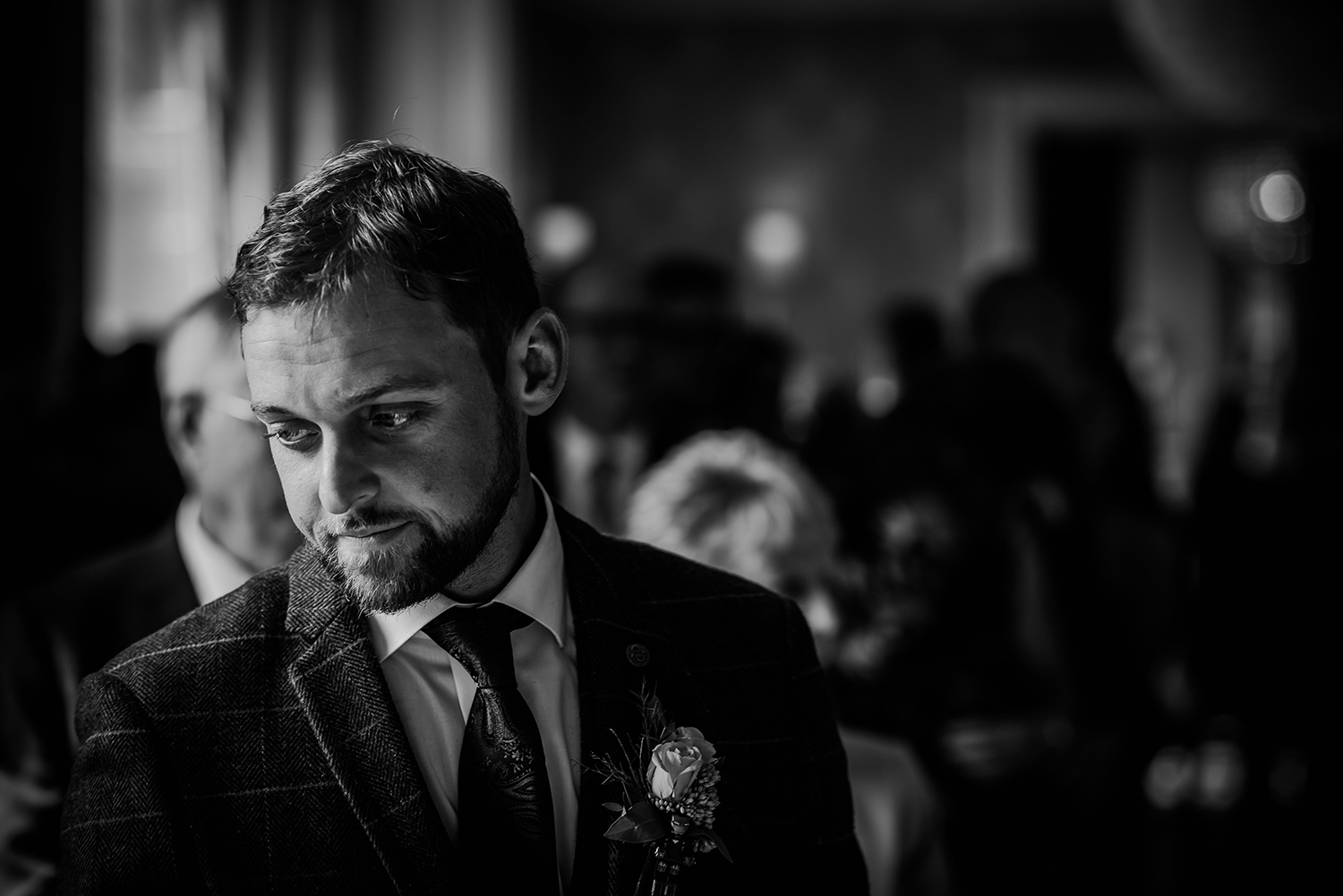 bw photo of the groom waiting for the bride