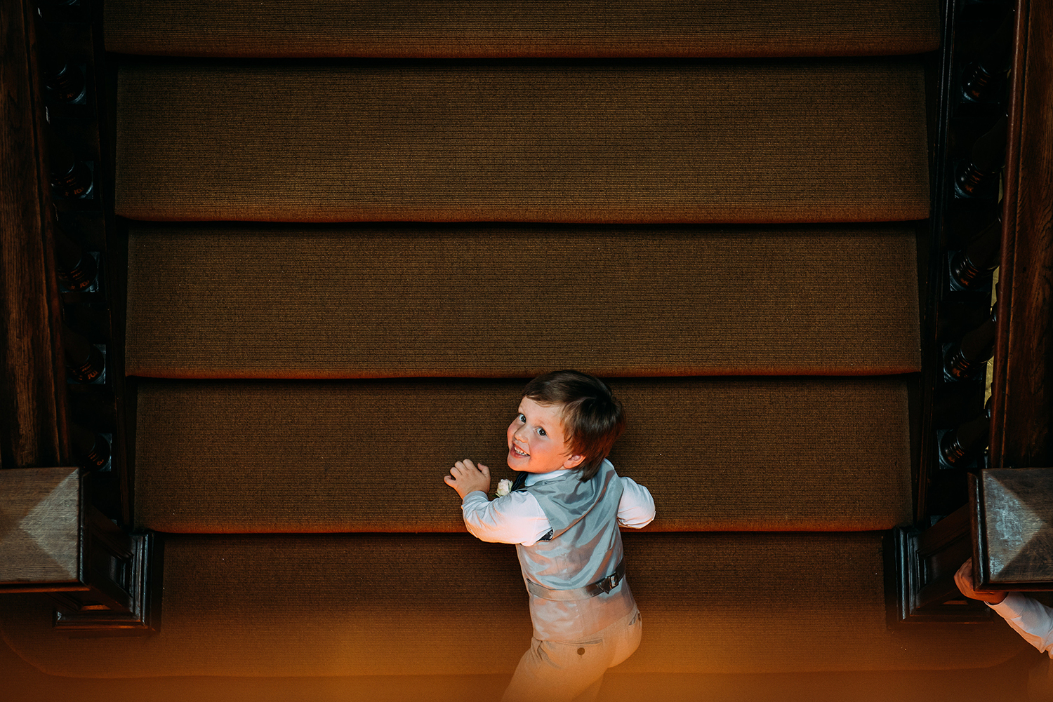 boy looking up at the camera from the stairs