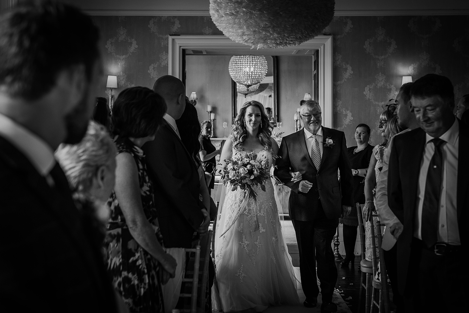 bw photo of bride and father walking down the aisle