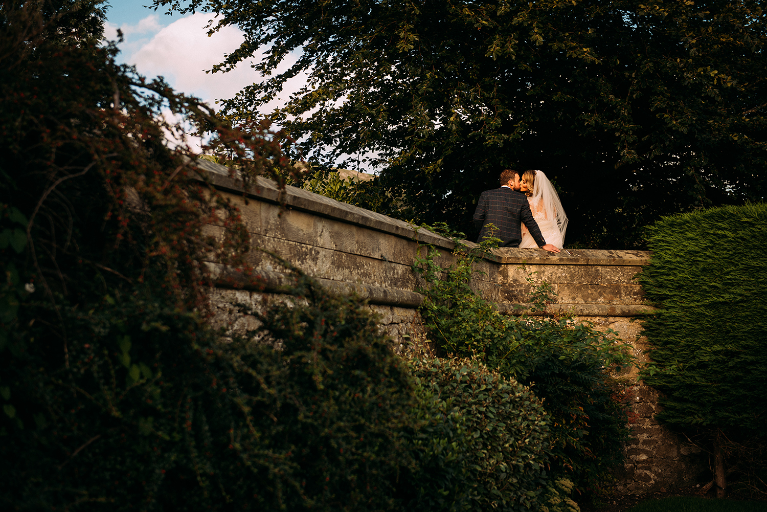 bride and groom kissing on a wall