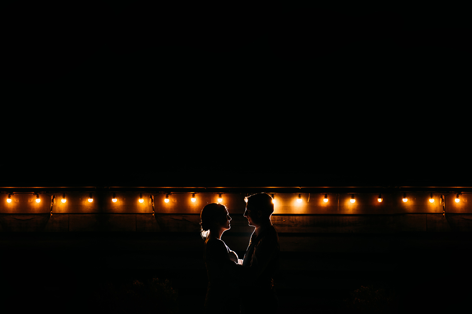 bride and groom night time portrait in front of some light bulbs