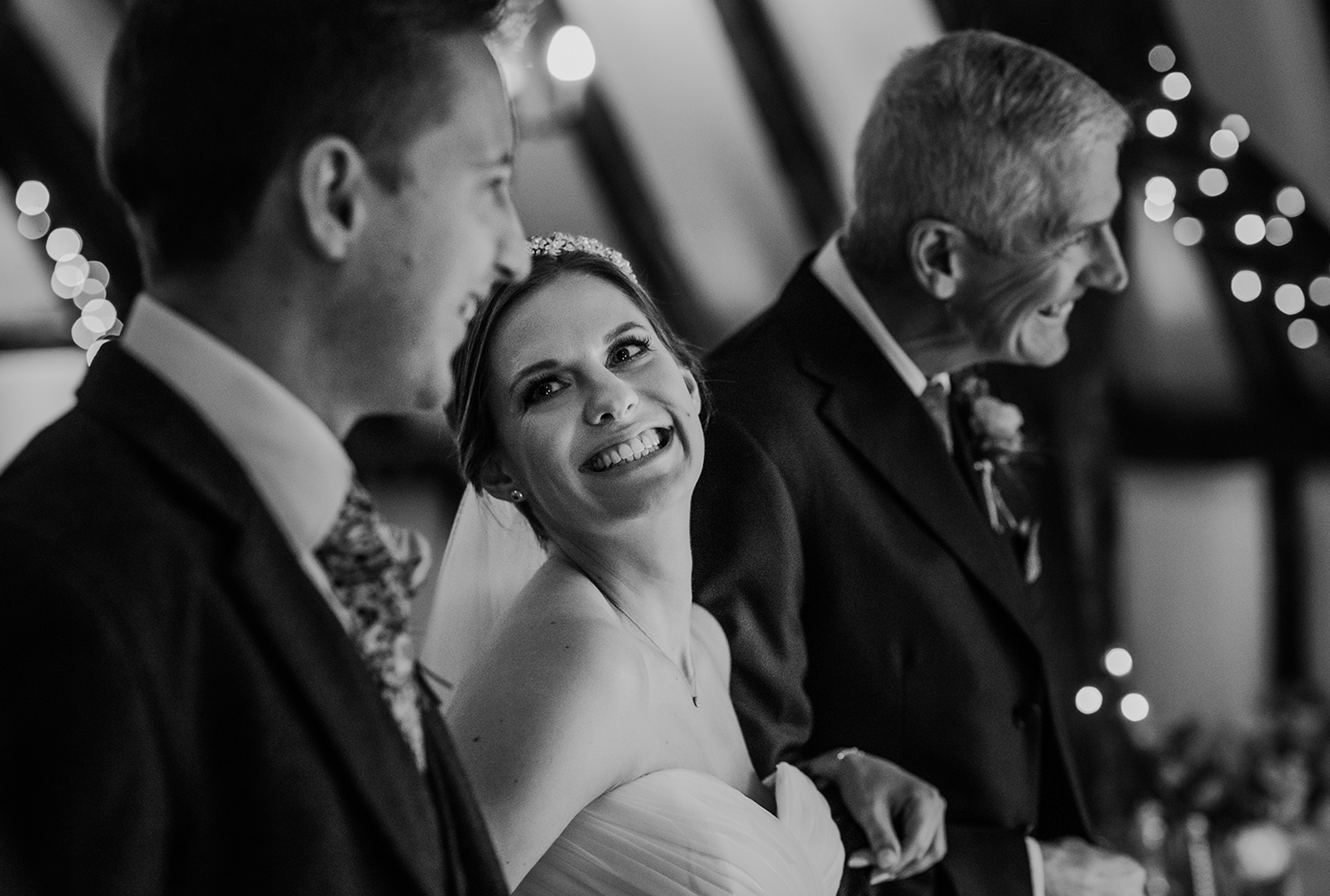 bride smiling at groom at the alter - bw photo