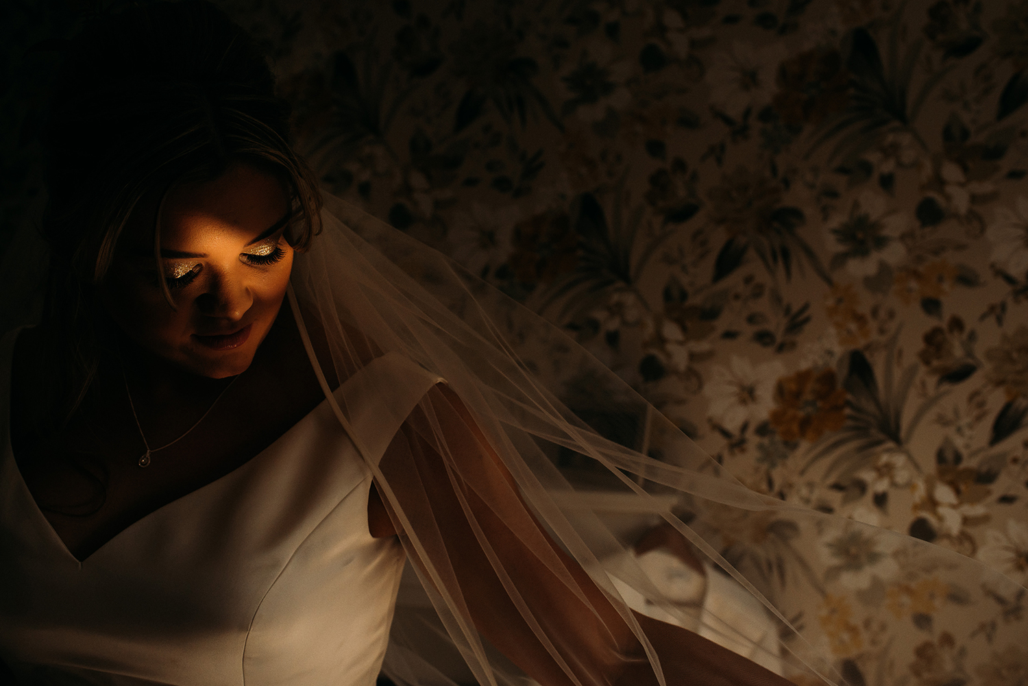 sunlight hitting the brides eyes as she plays with her veil