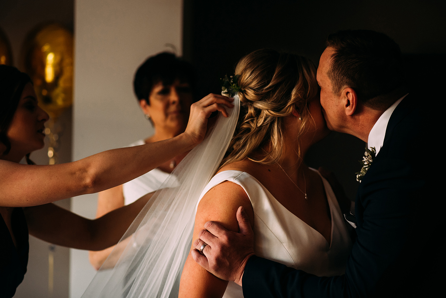 bride and her dad kiss as her sister adjusts her veil