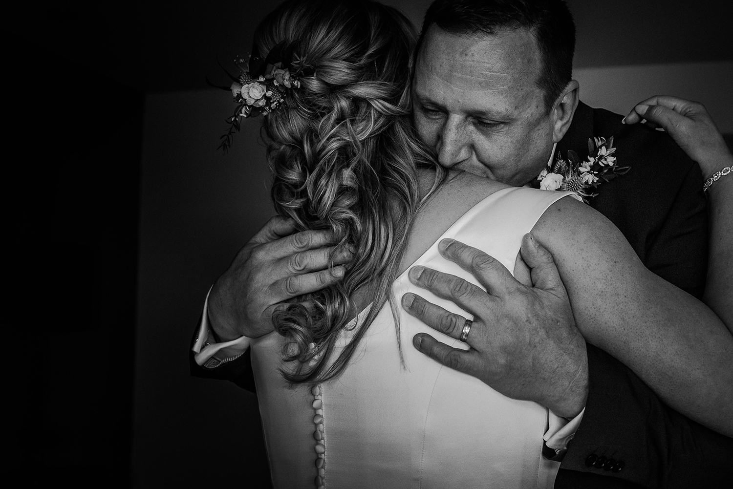 bw photo of the brides dad giving her a big hug