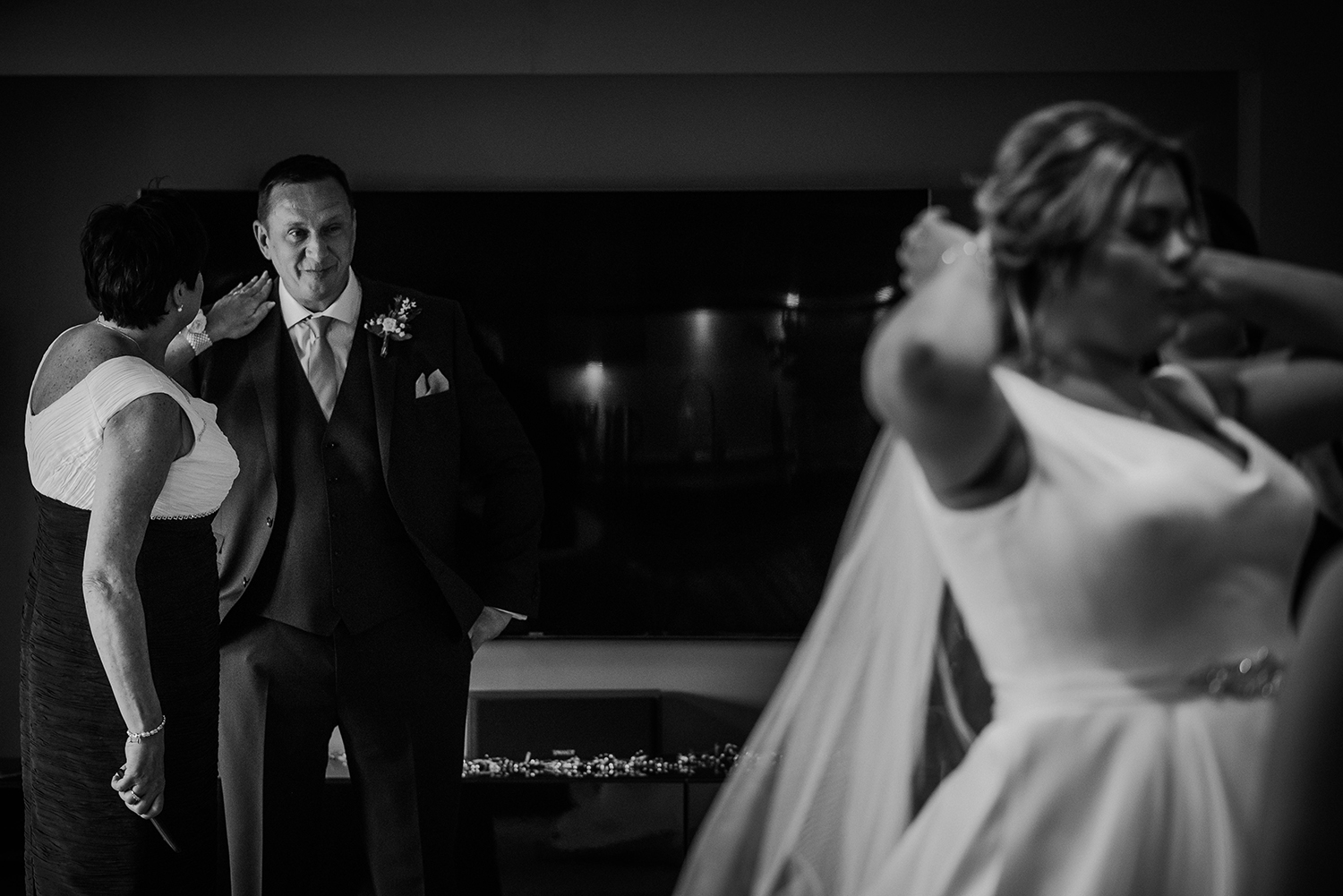 BW photo of brides mother comforting her husband as he looks proudly at his daughter in the foreground
