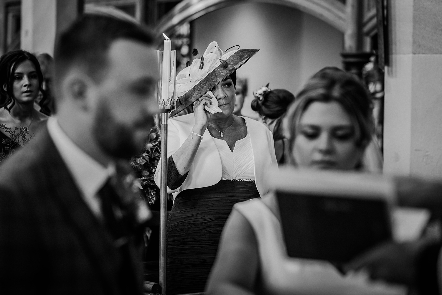bw photo of brides mum wiping a tear in church