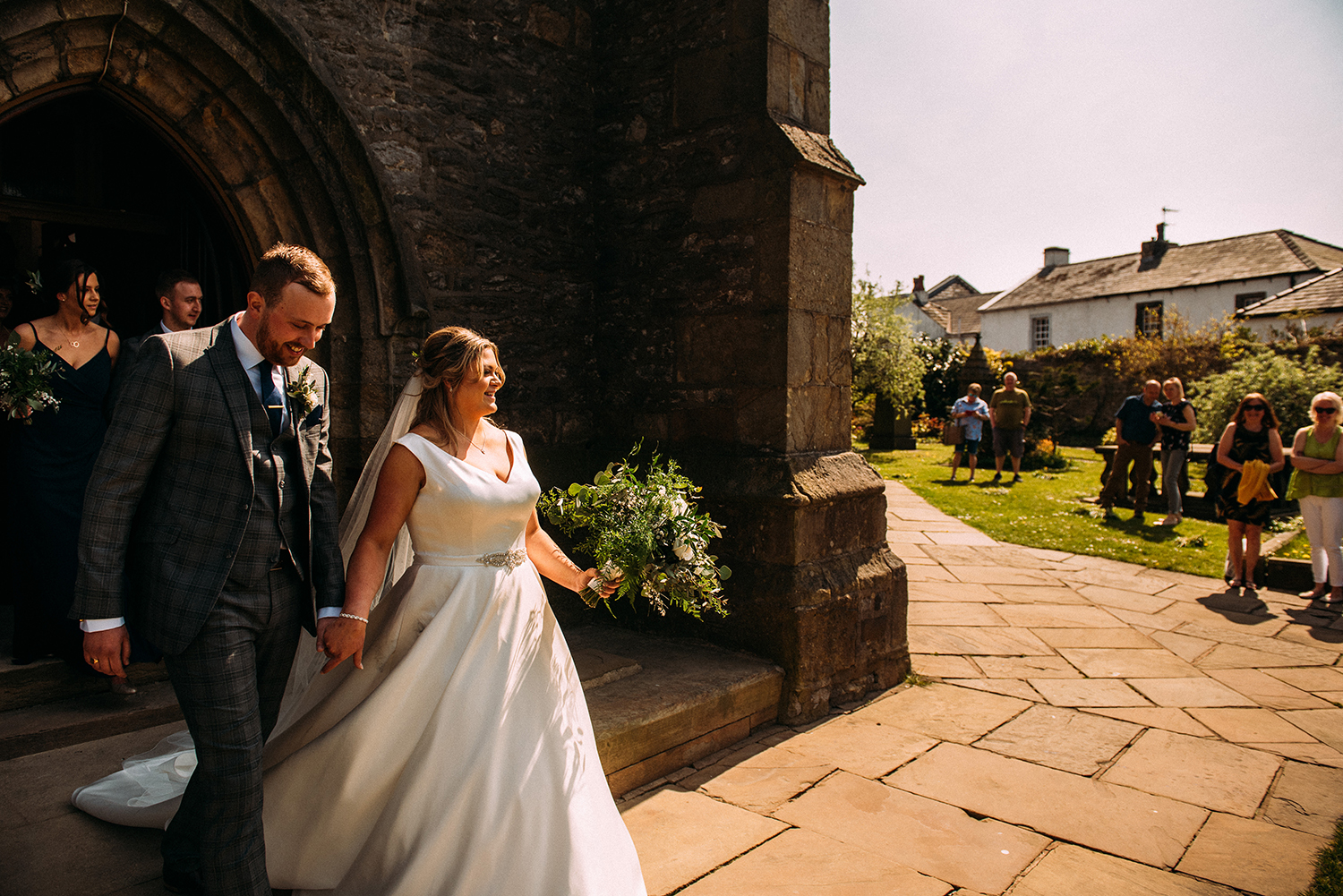 bride and groom leave church in the sunlight with the public looking on