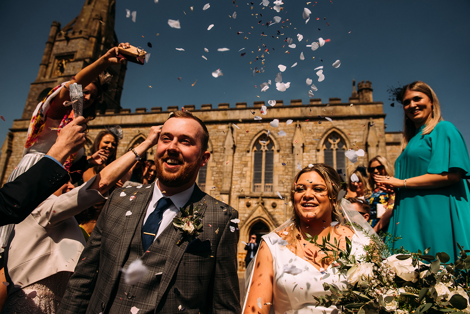 bride and groom walk through confetti outside church